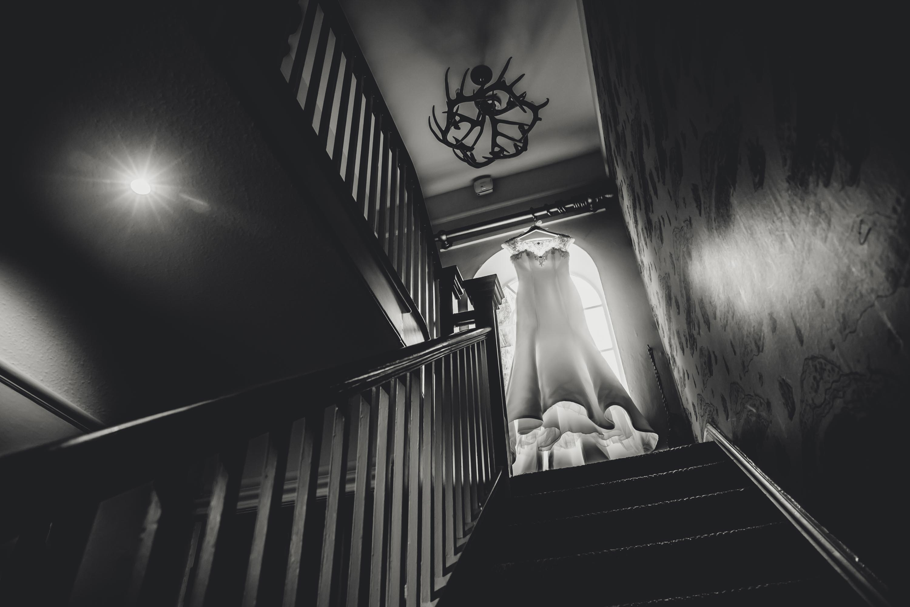 wedding dress at the top of the stairs at lodge at eaves hall in clitheroe