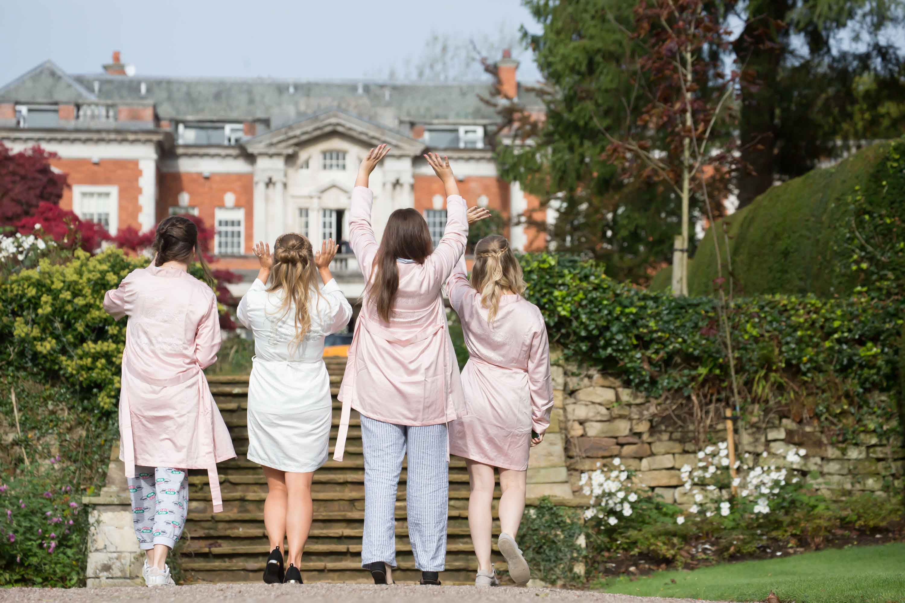 bride and bridesmaid walk up to the eaves hall georgian mansion