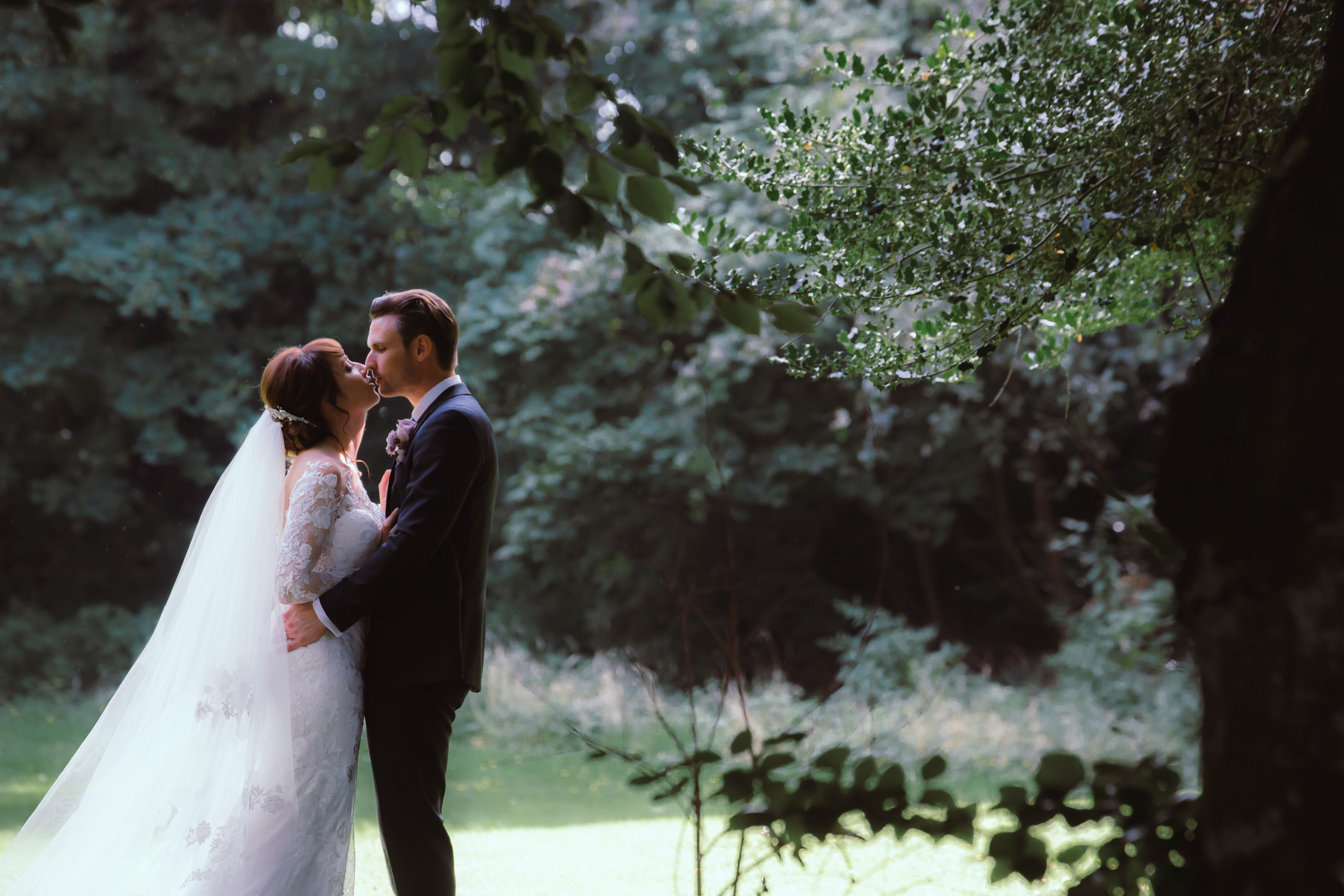 gorgeous bride kisses groom in romantic light in the woods