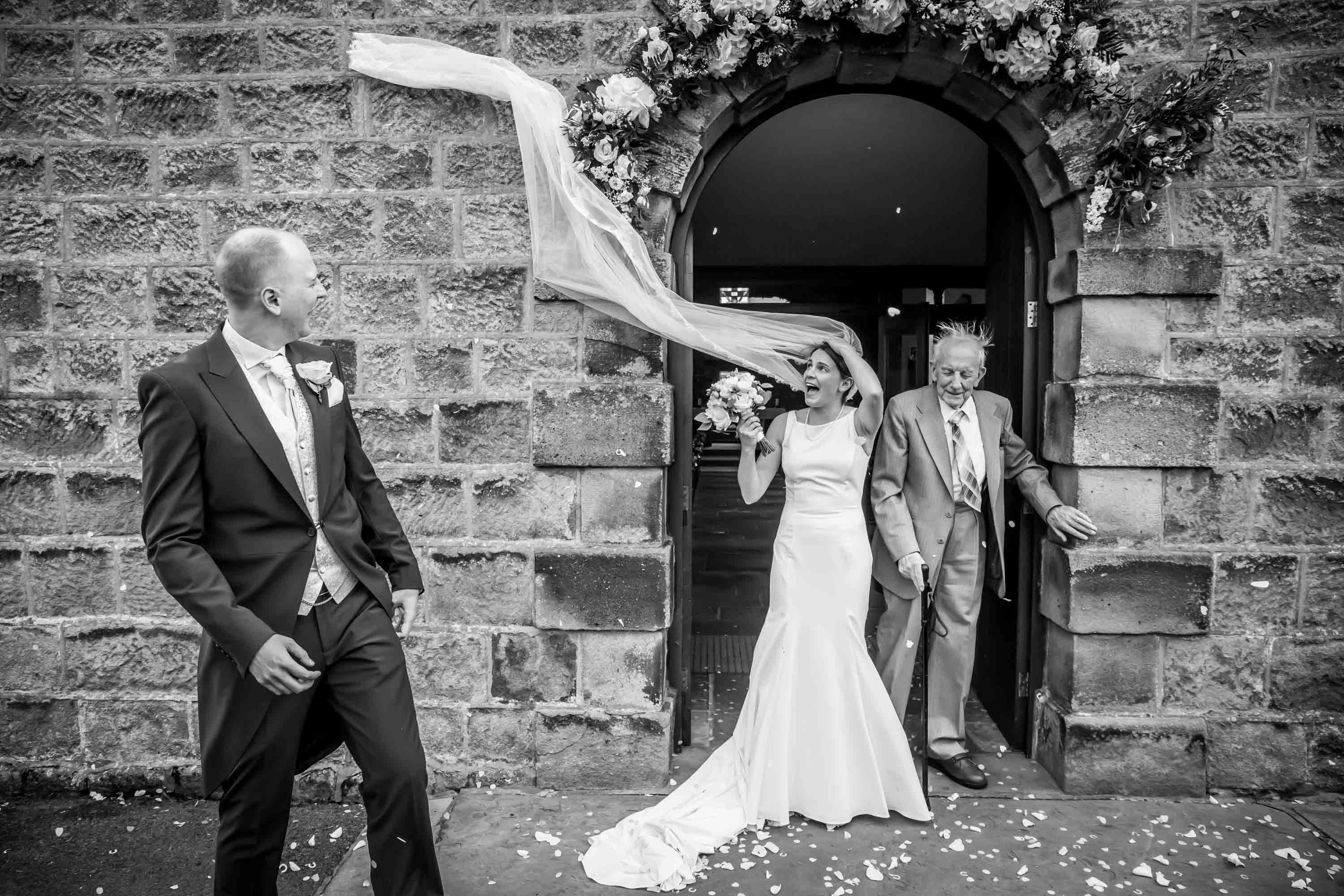 brides veil gets caught on church wall in geometric shape wall as she comes out of doorway