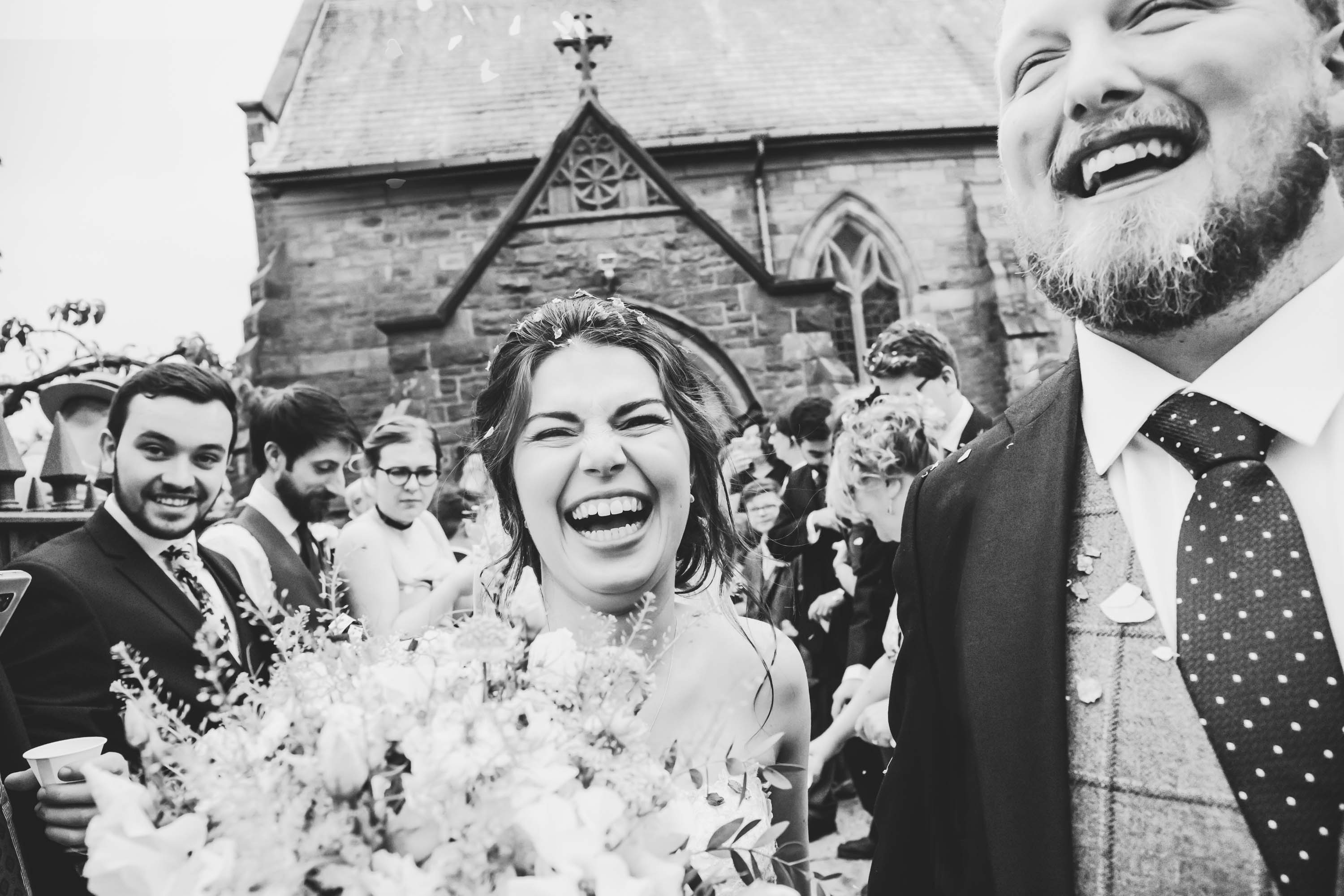 couple exit church with big happy smiles after being showered in confetti
