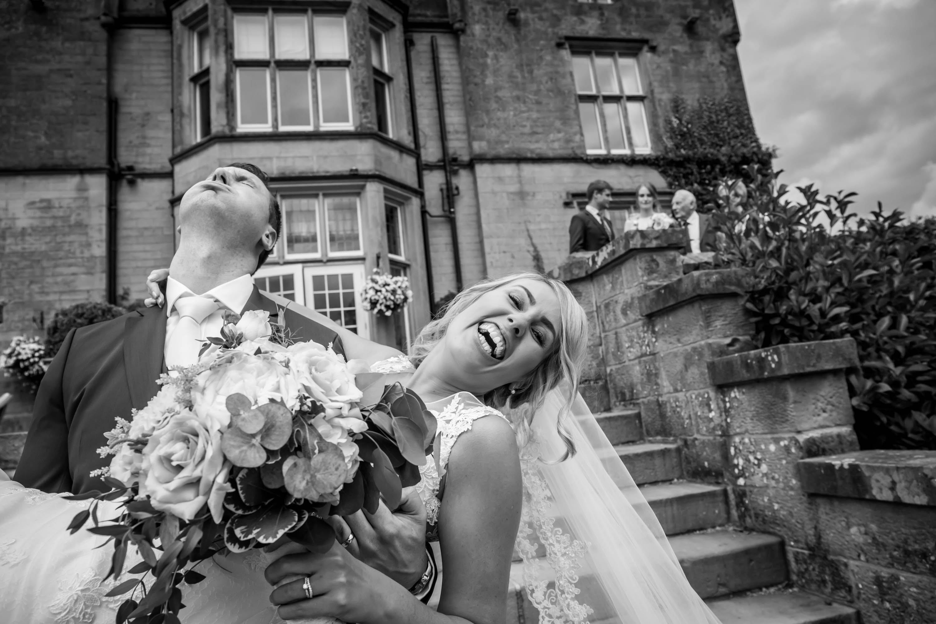 groom puffs out air as he picks up the bride who is laughing