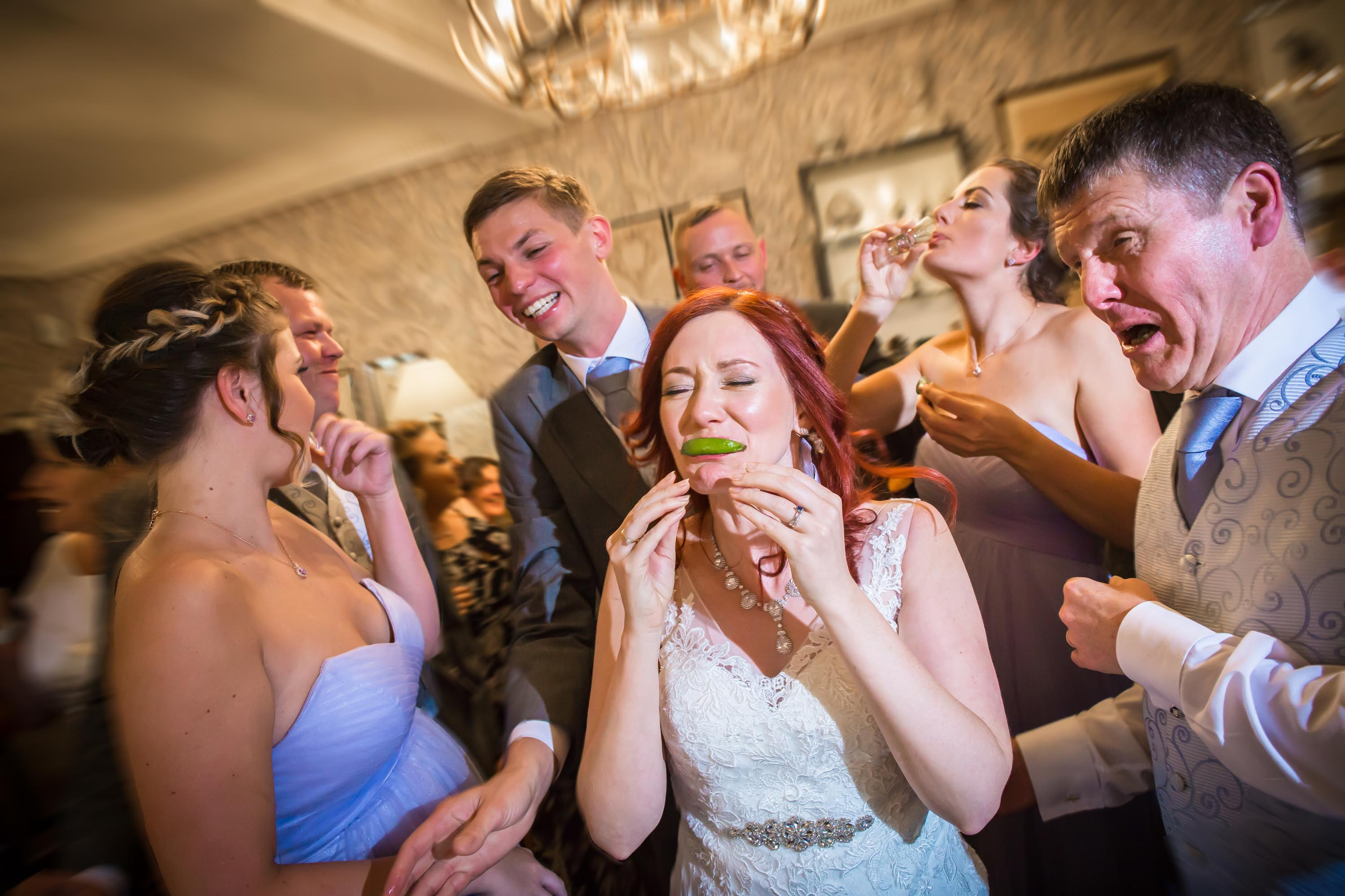 bride and groom do slammers at the bar with wedding guests
