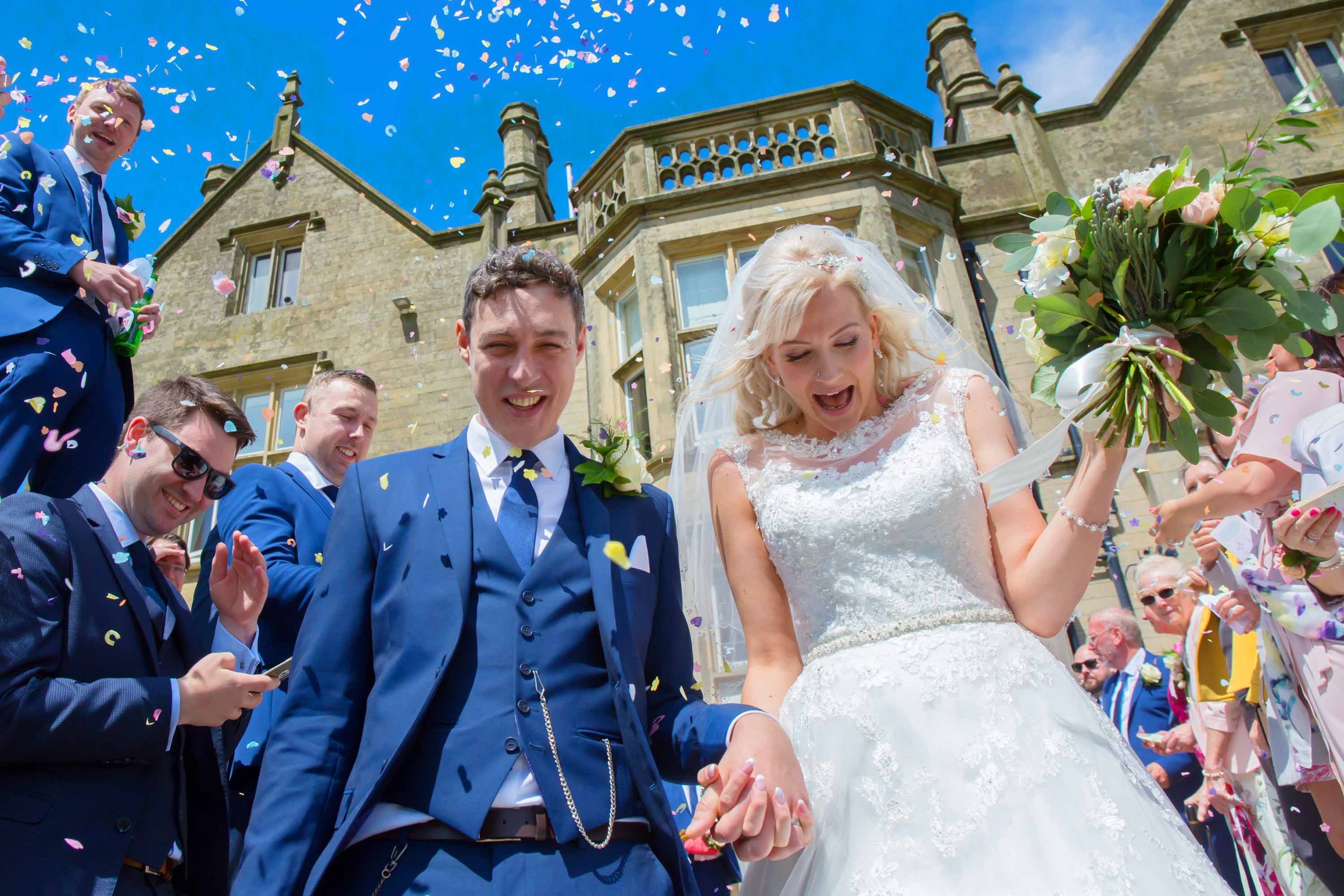 bride and groom are showered in confetti on the steps of falcon manor in settle