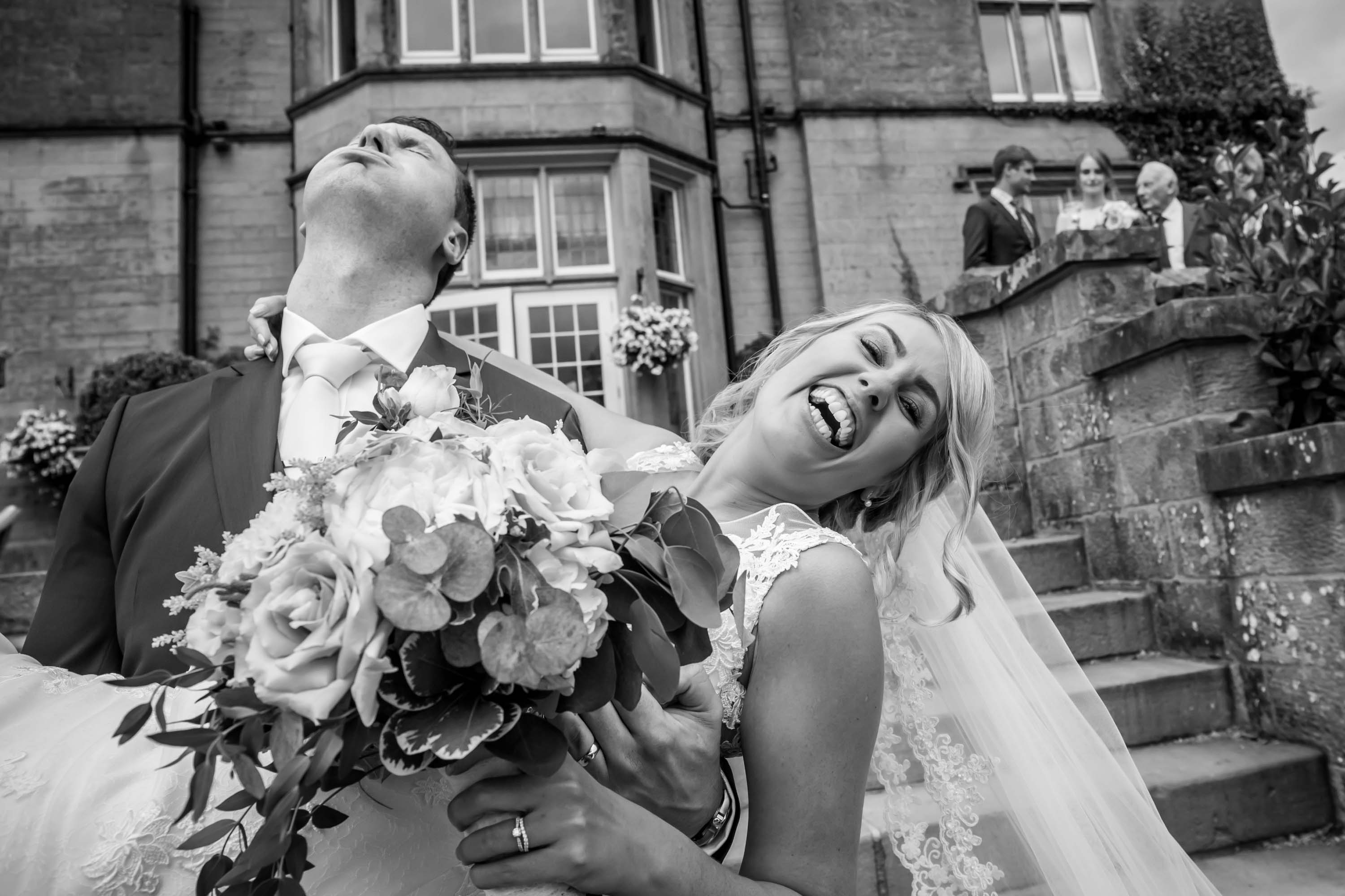 bride and groom have fun on the steps of falcon manor
