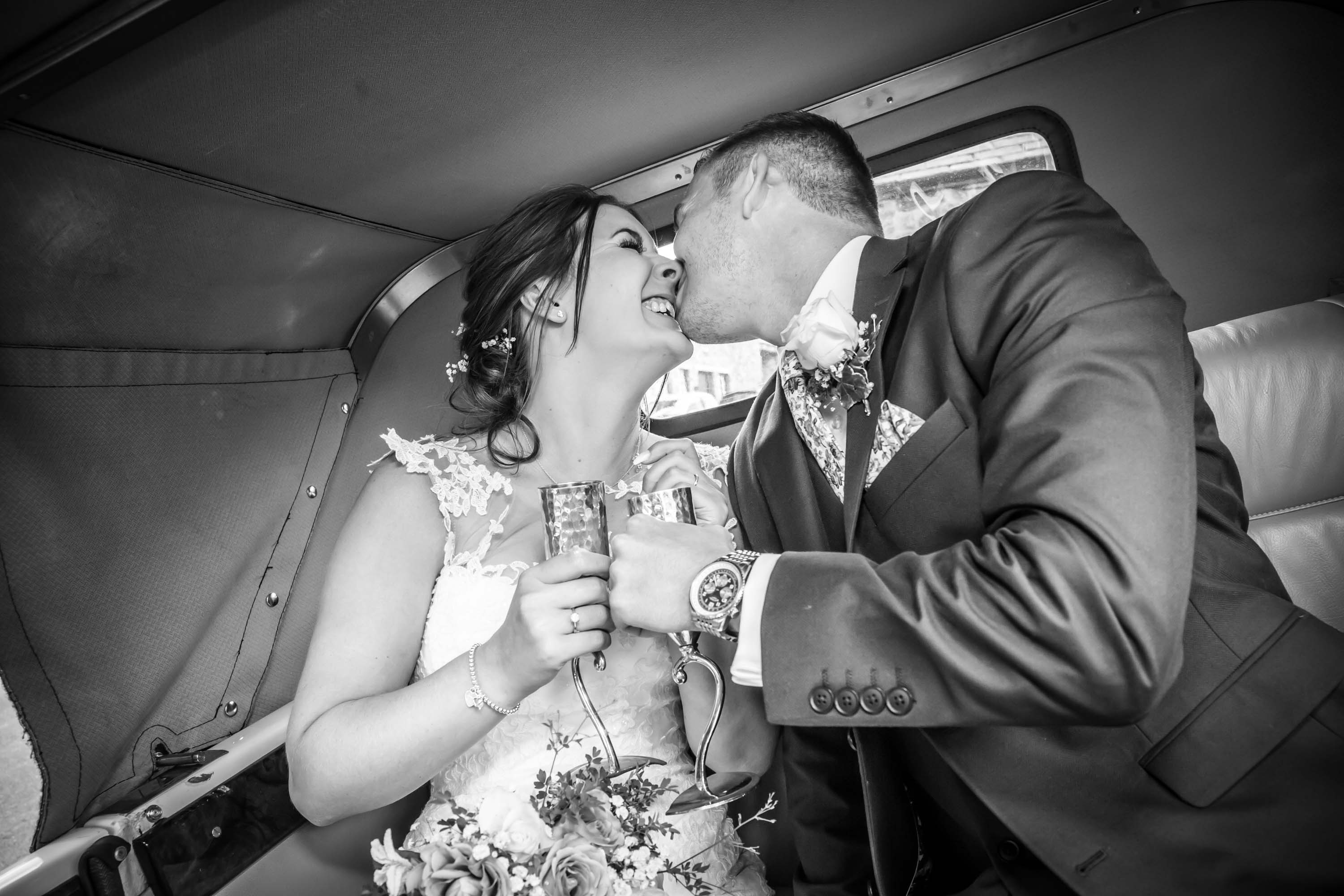 bride and groom kiss and laugh in back of wedding car