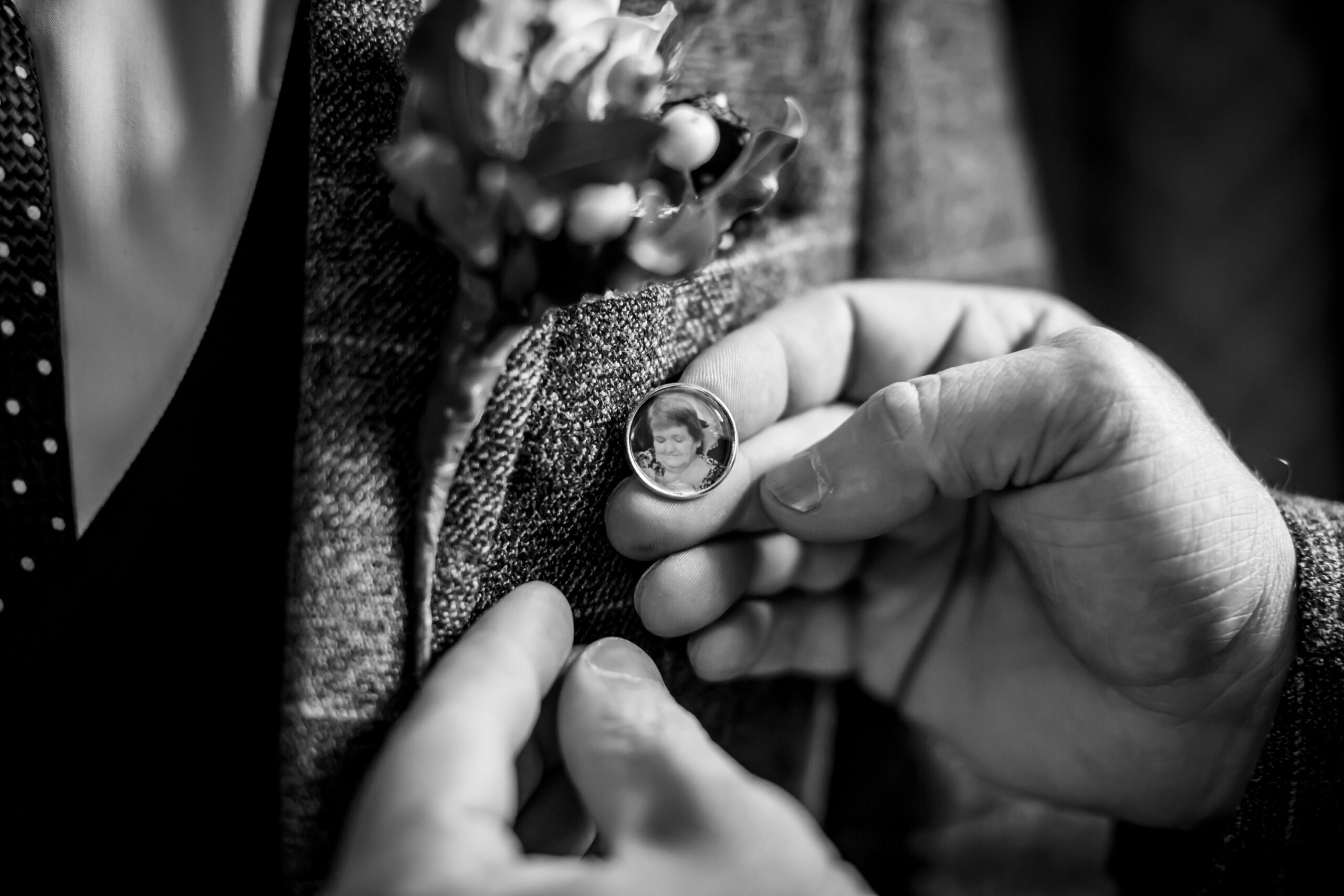 groom has broach with photo of his grandma in attached to his wedding suit