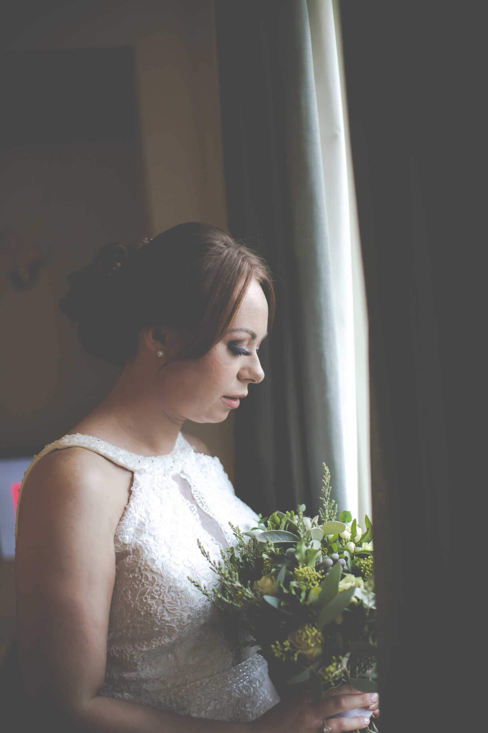 bride looks at her flowers with beautiful window light at gretna green hotel