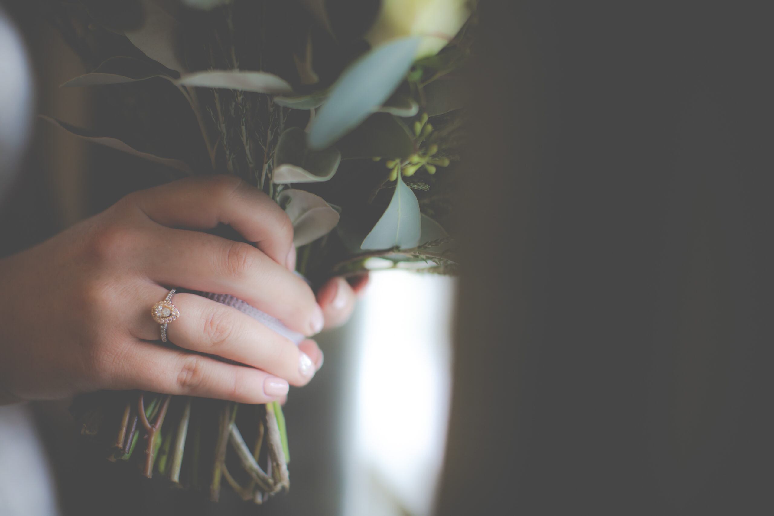 close up of brides engagement ring as she hold her wedding bouquet