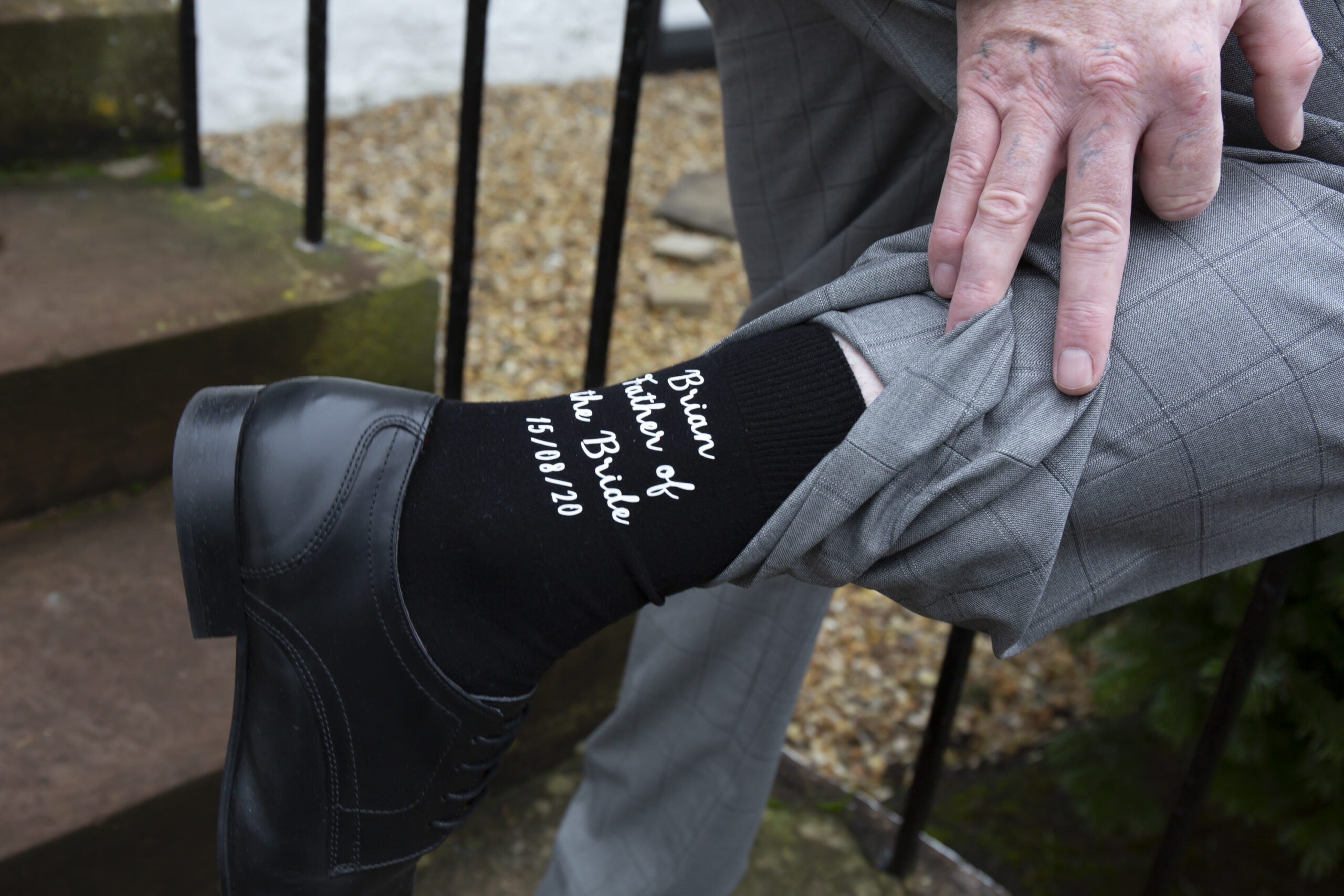 father of the bride shows off his special wedding socks