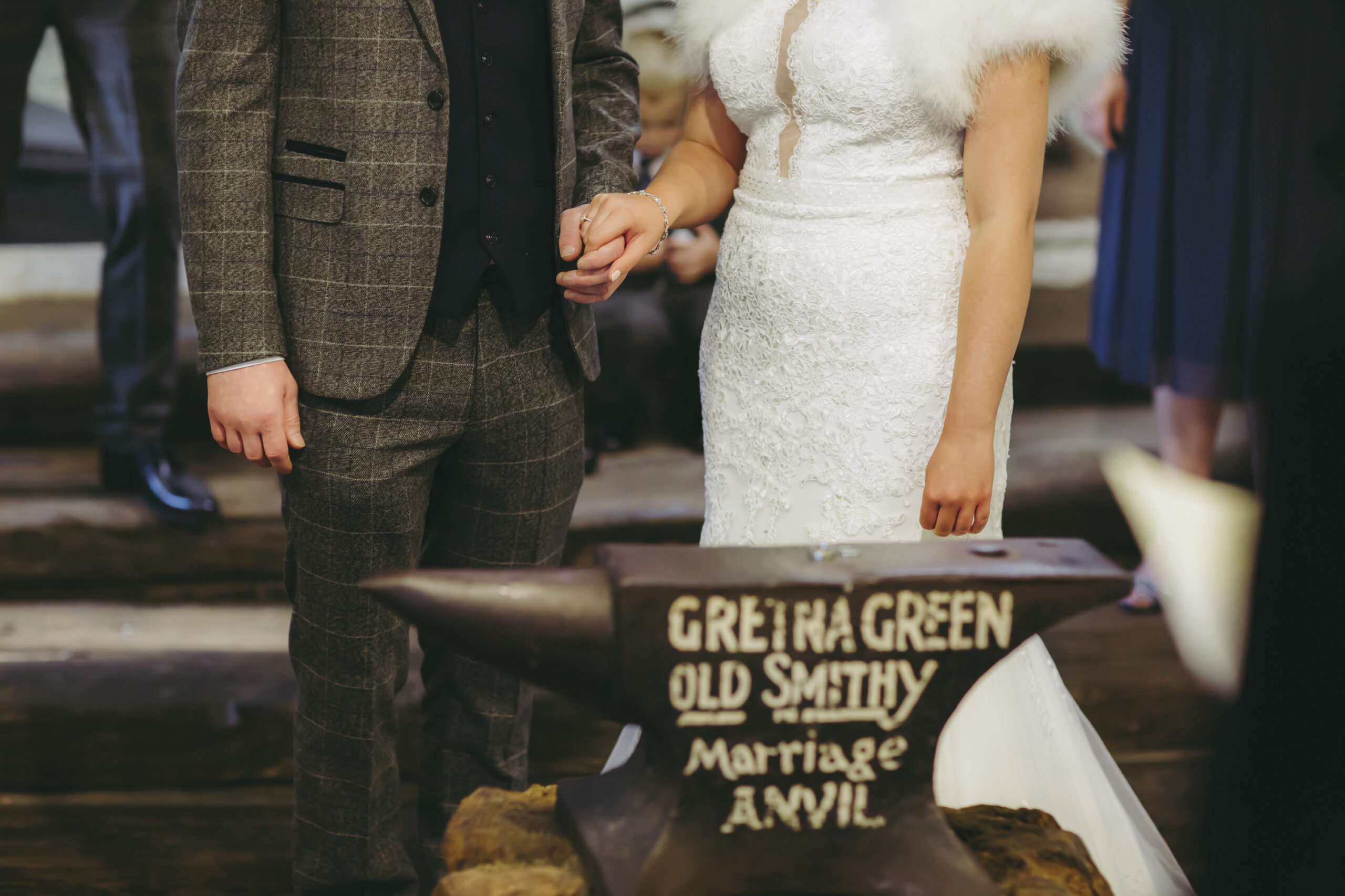 bride and groom hold hands at the gretna green old smithy marriage anvil