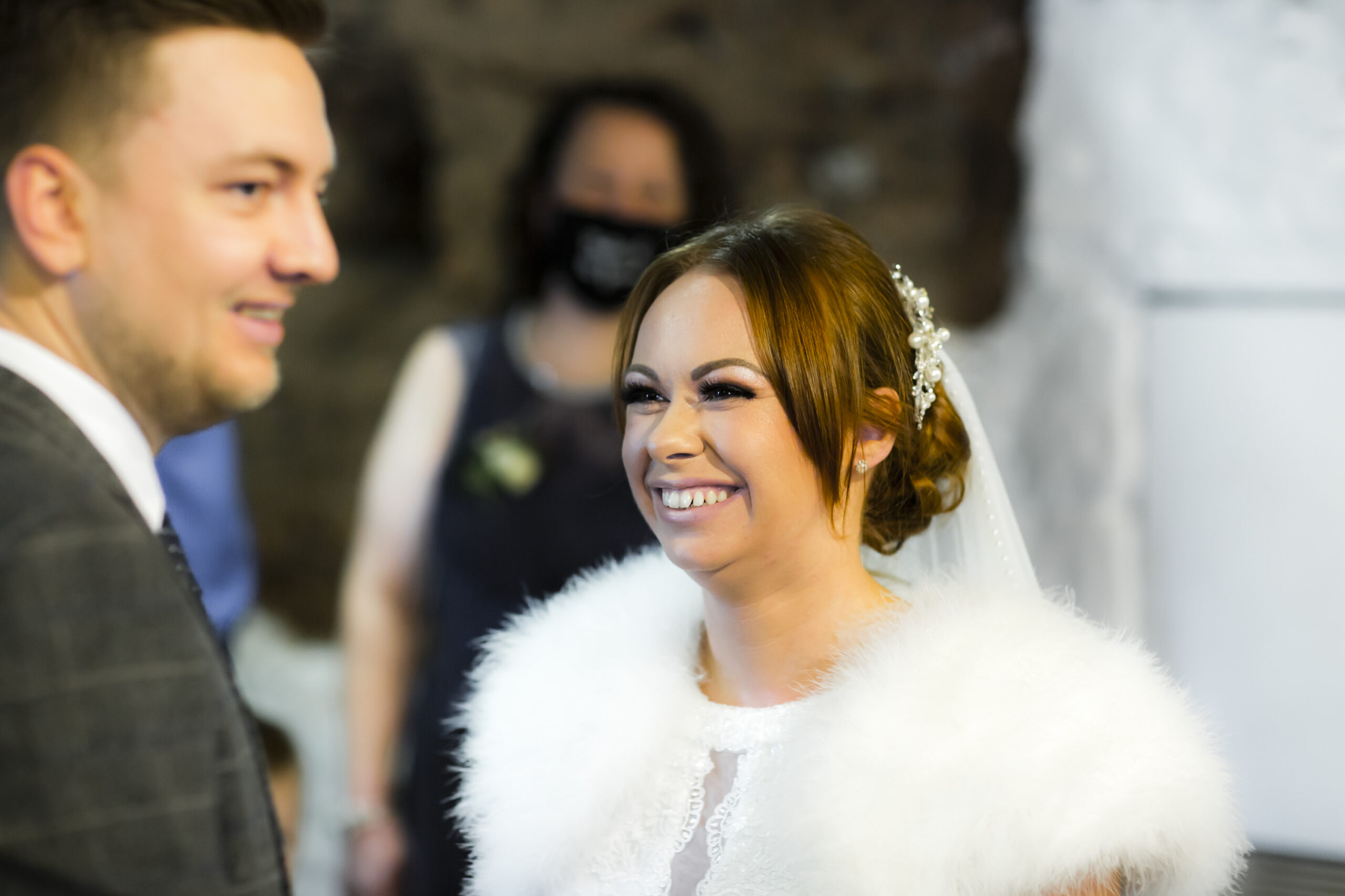 happy bride looks at groom at marriage ceremony at blacksmiths old shop in gretna green