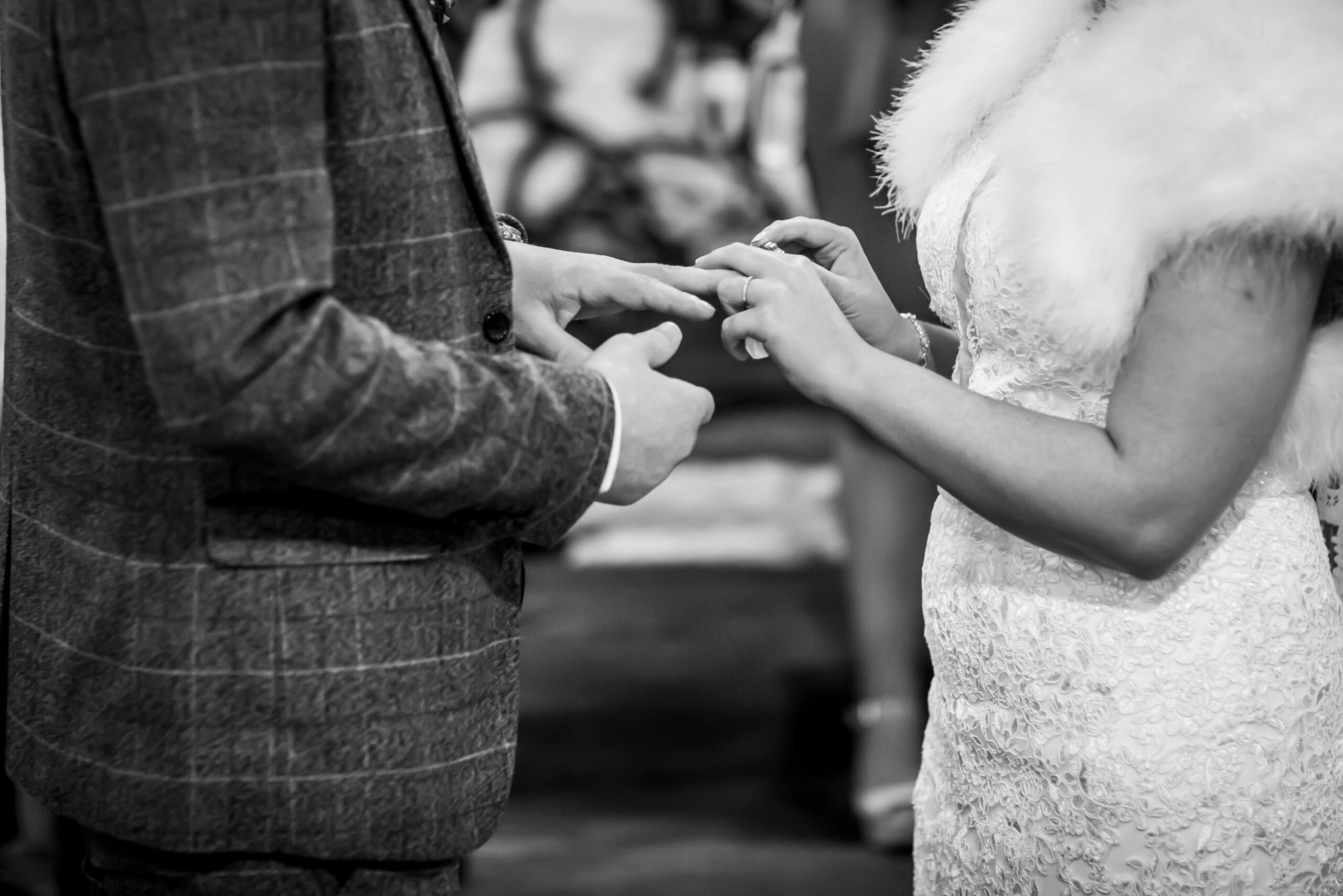bride puts wedding ring on grooms finger at marriage ceremony at blacksmiths old shop in gretna green