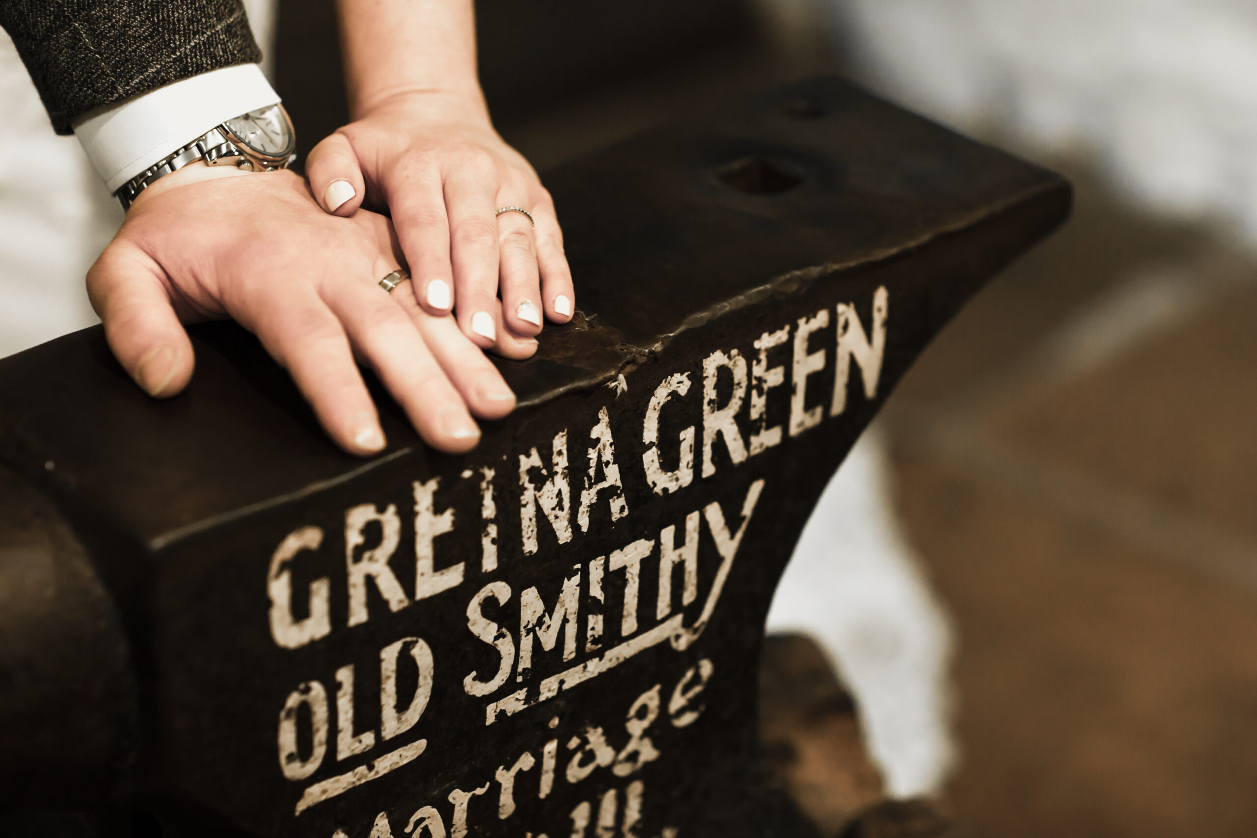 bride and groom put hands on gretna green old smithy marriage anvil