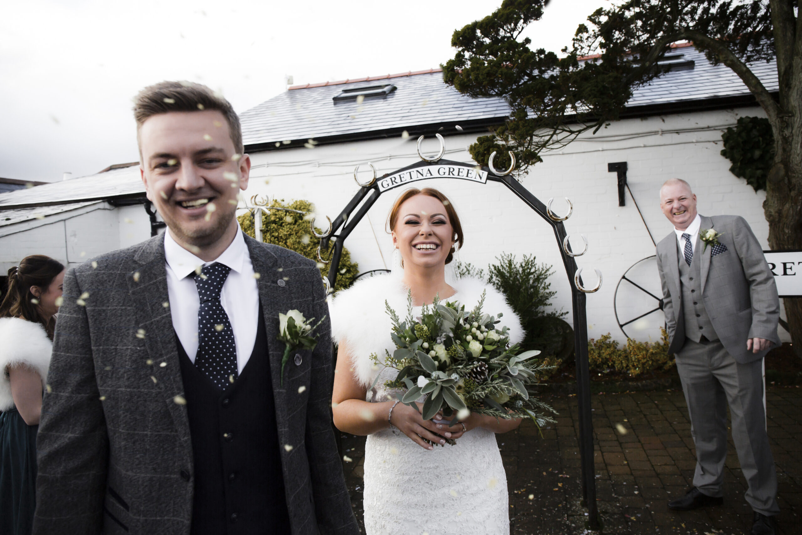 happy bride and groom showered in confetti outside the old blacksmiths shop in gretna green