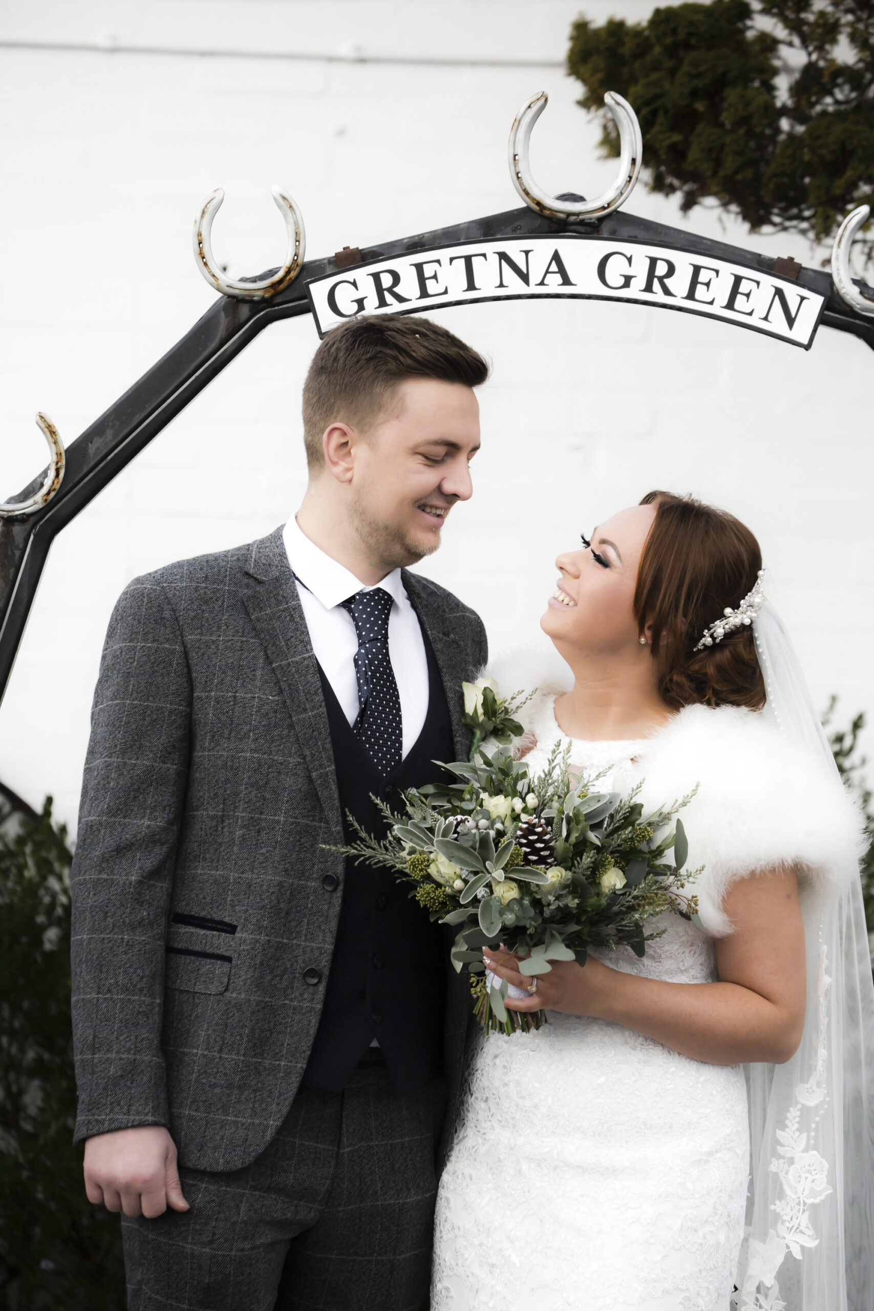 happy bride and groom under the gretna green sign at the old blacksmiths shop