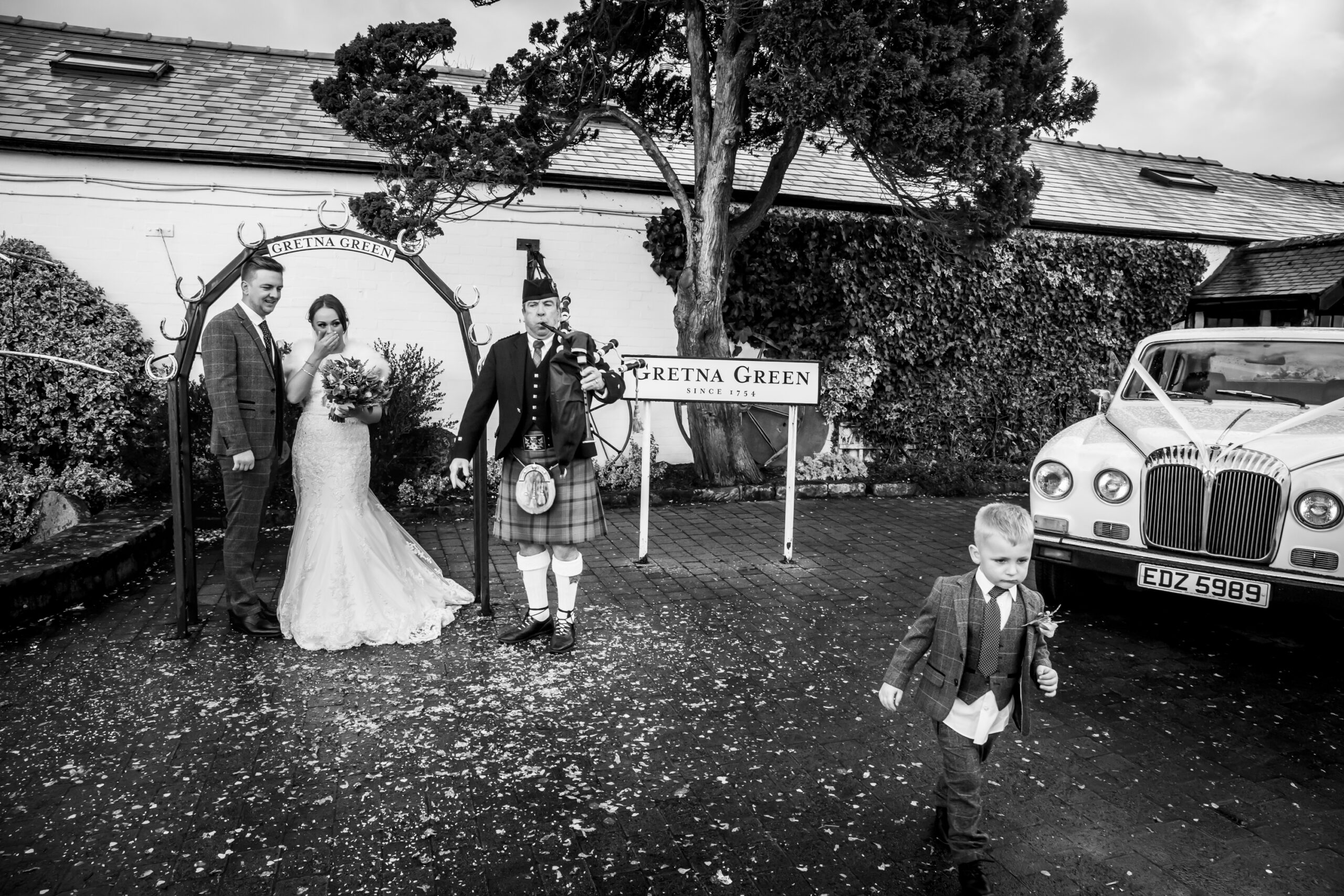 bride laughs as page boy walks away while piper plays bagpipes at gretna green