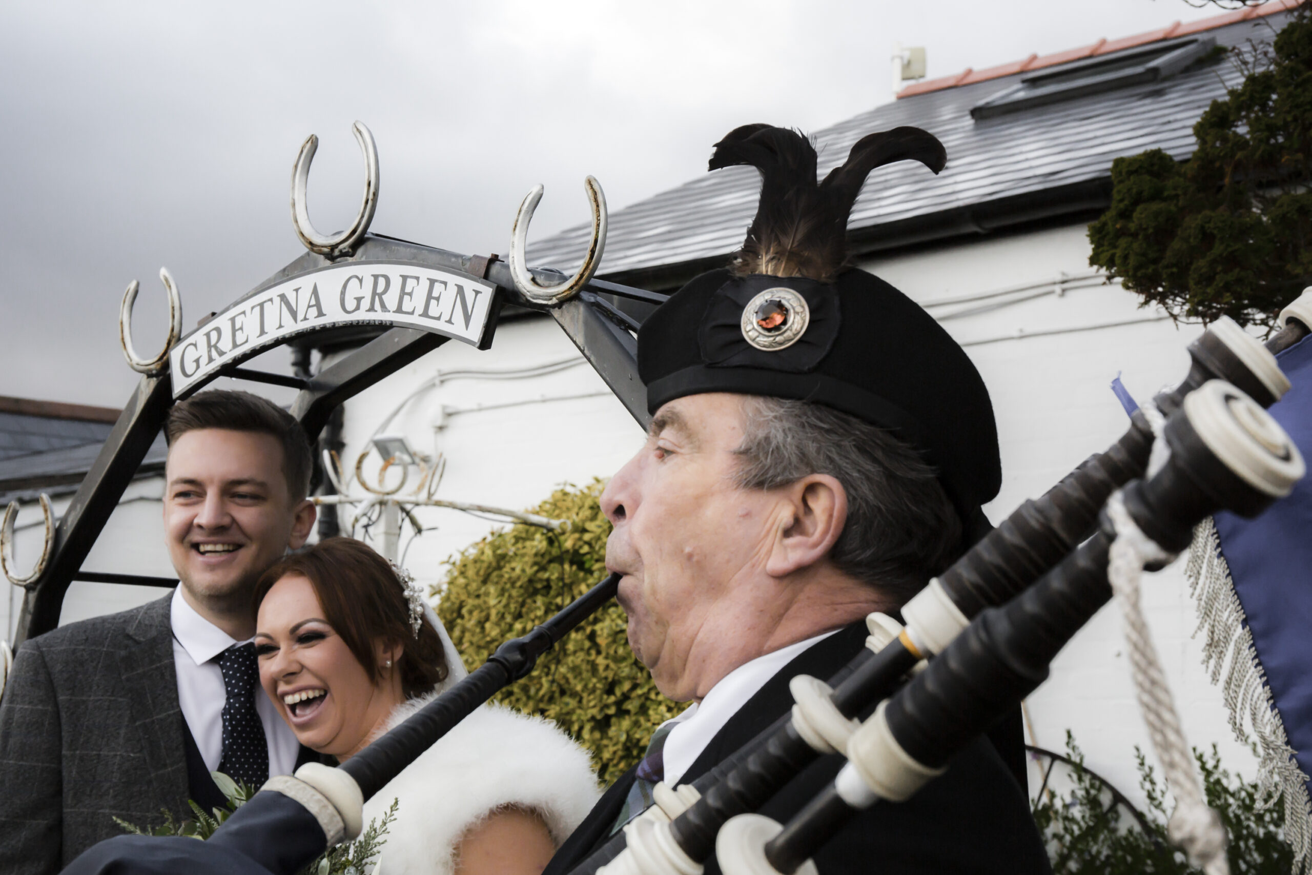 bride laughs while piper plays bagpipes at gretna green