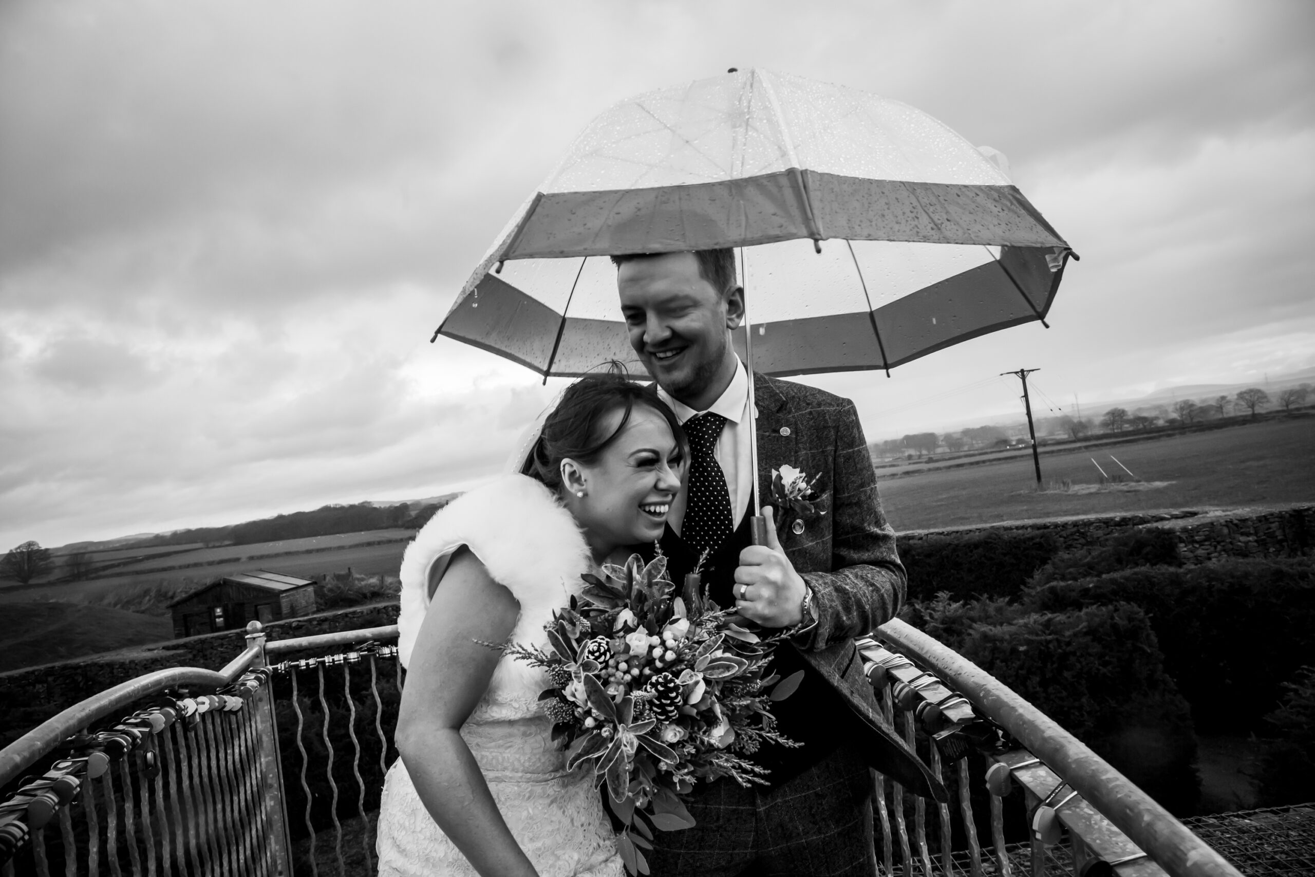 bride and groom laugh next to the marriage anvil in the lovers maze at gretna green