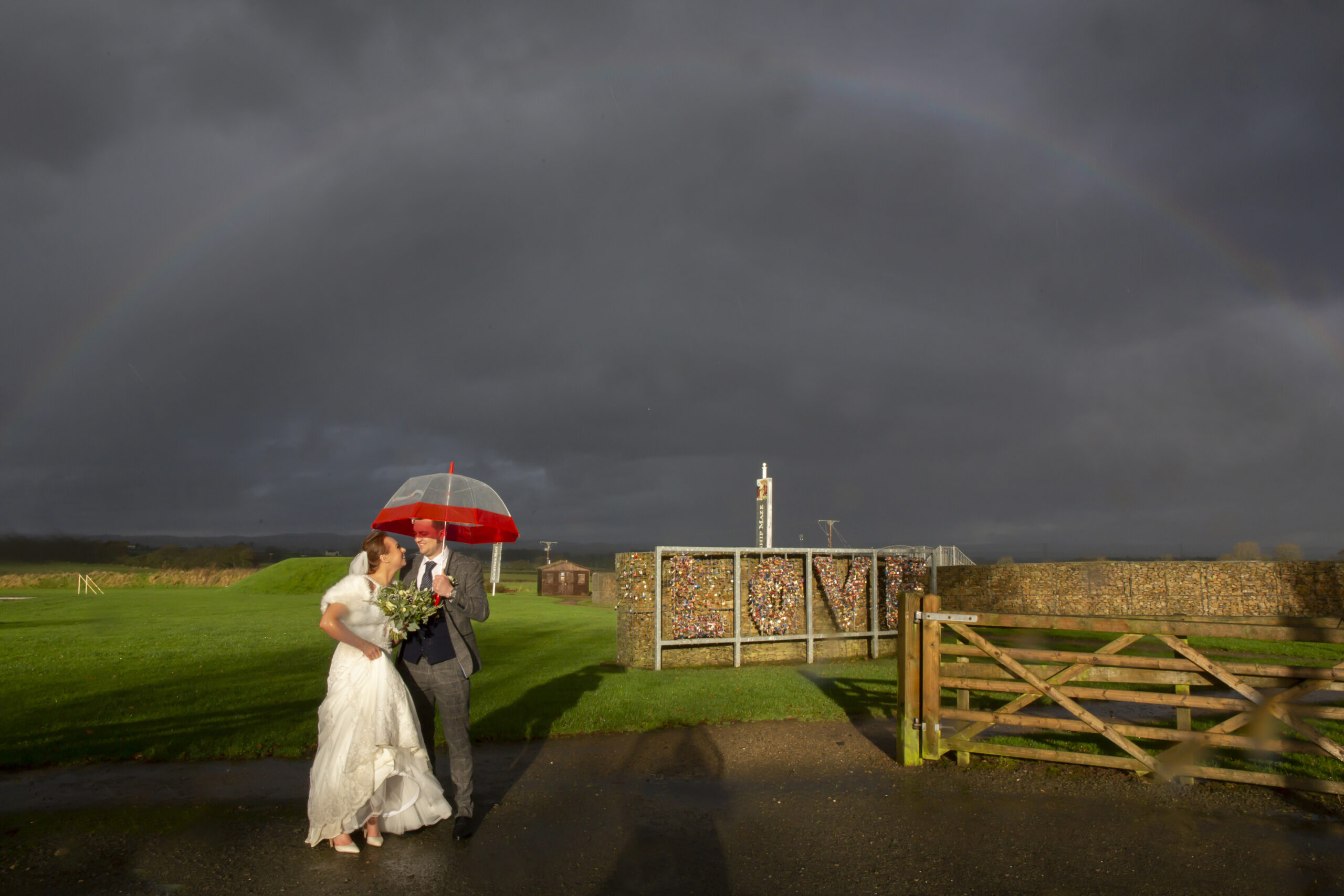bride and groom under a rainbow near the courtship maze at gretna green