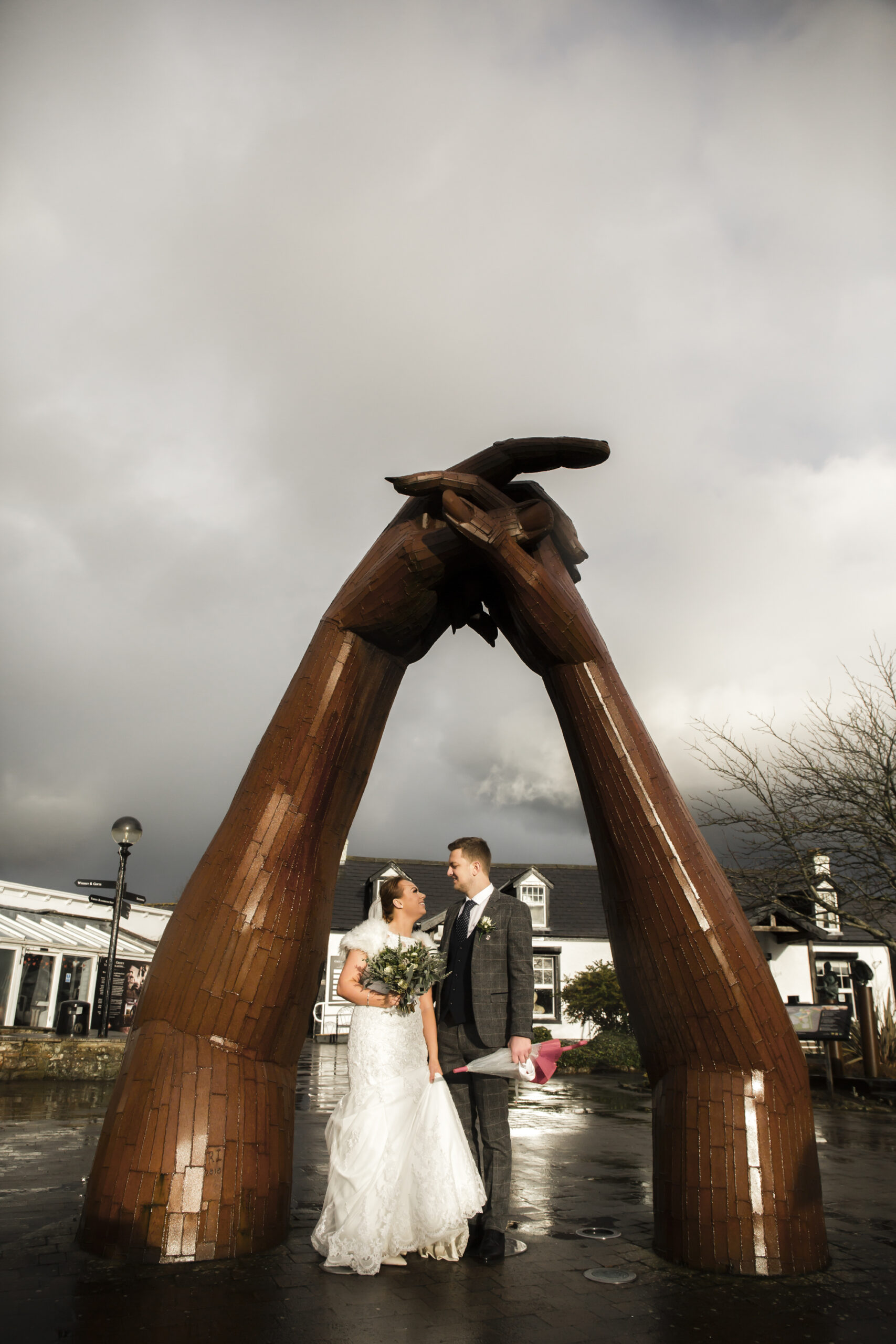 bride and groom under the big dance hands statue at gretna green