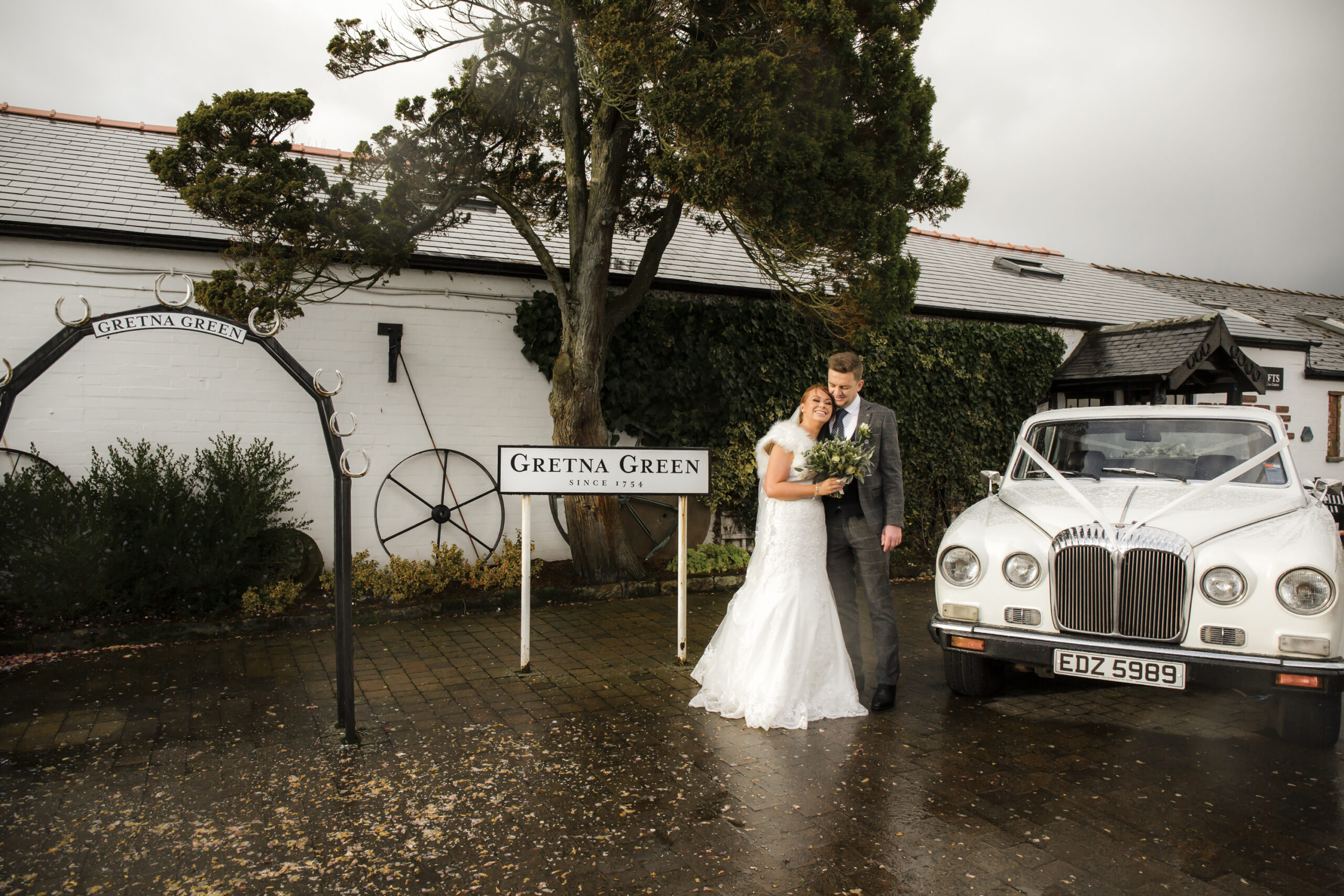 bride and groom outside the famous blacksmith shop next to wedding car at gretna green