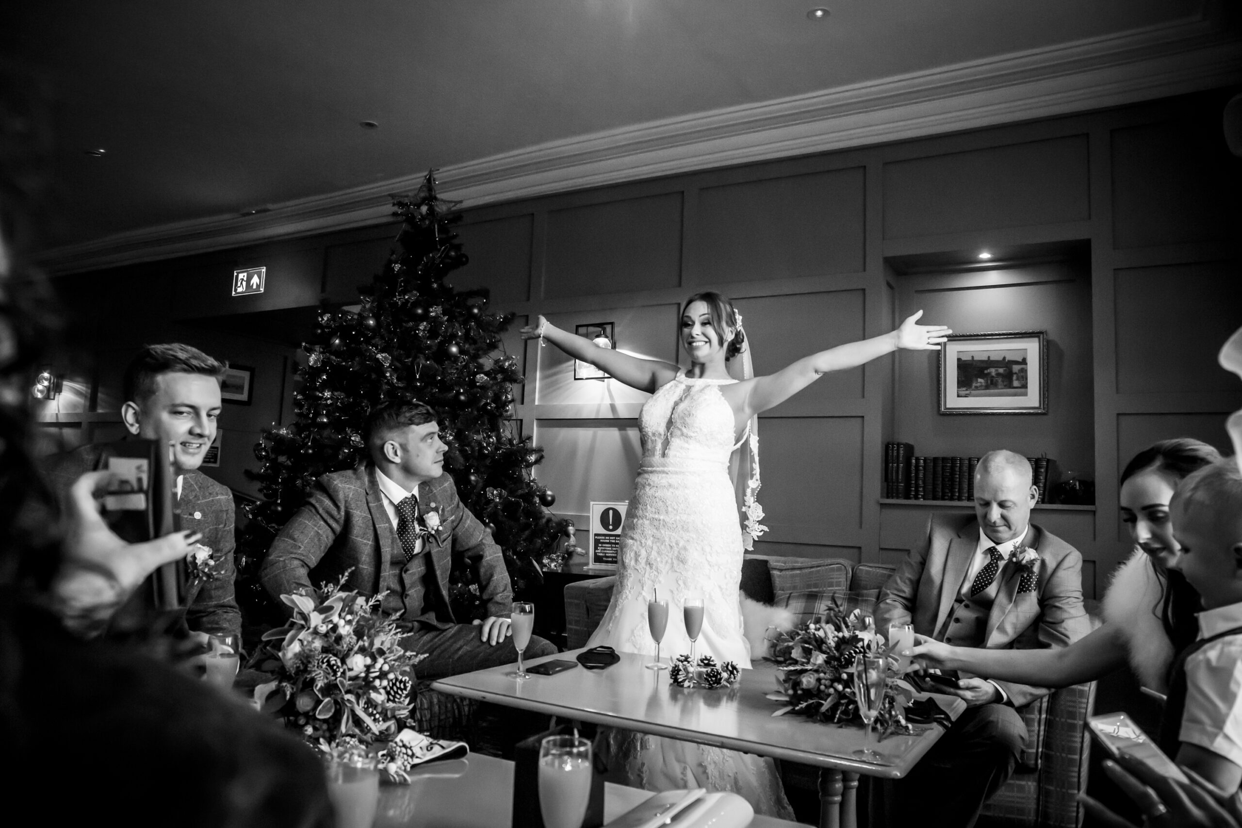 bride strikes victory pose for someone on a mobile phone at gretna green hotel
