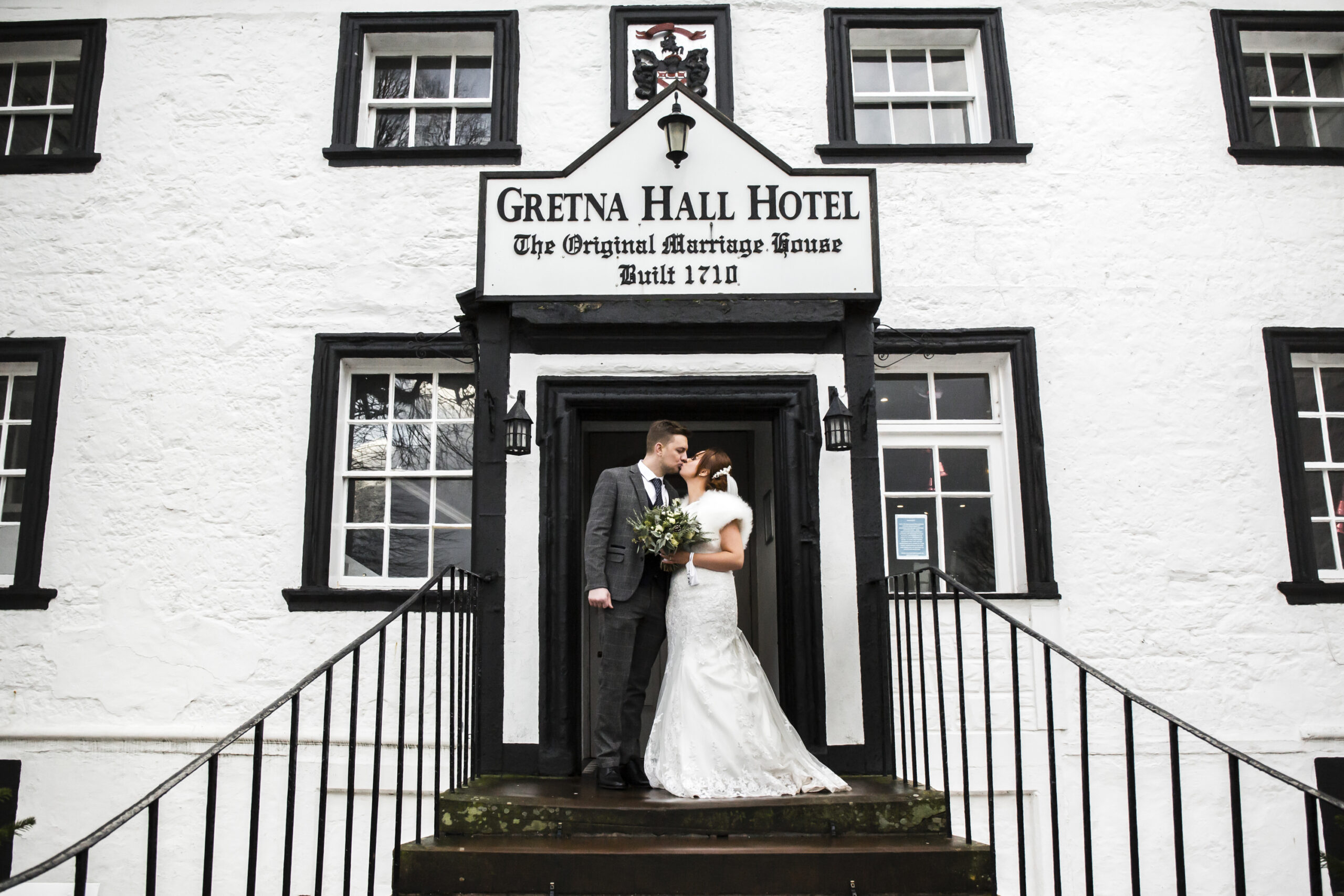 bride and groom portrait on the steps of the gretna green hotel