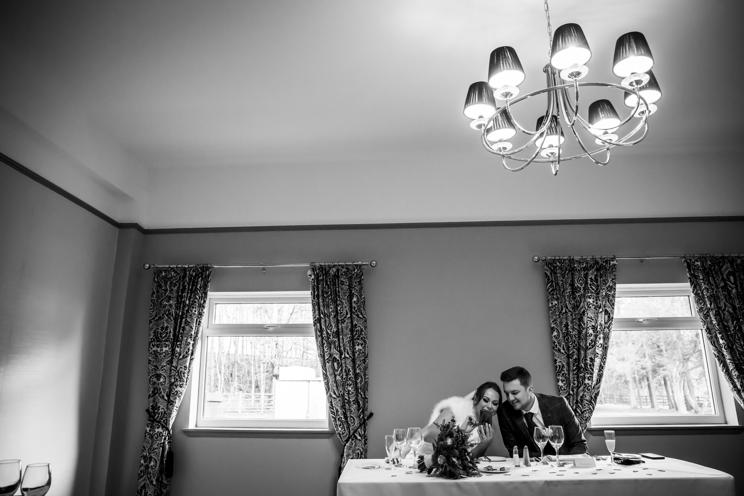 bride and groom look at their phone together at the wedding reception at gretna green hotel