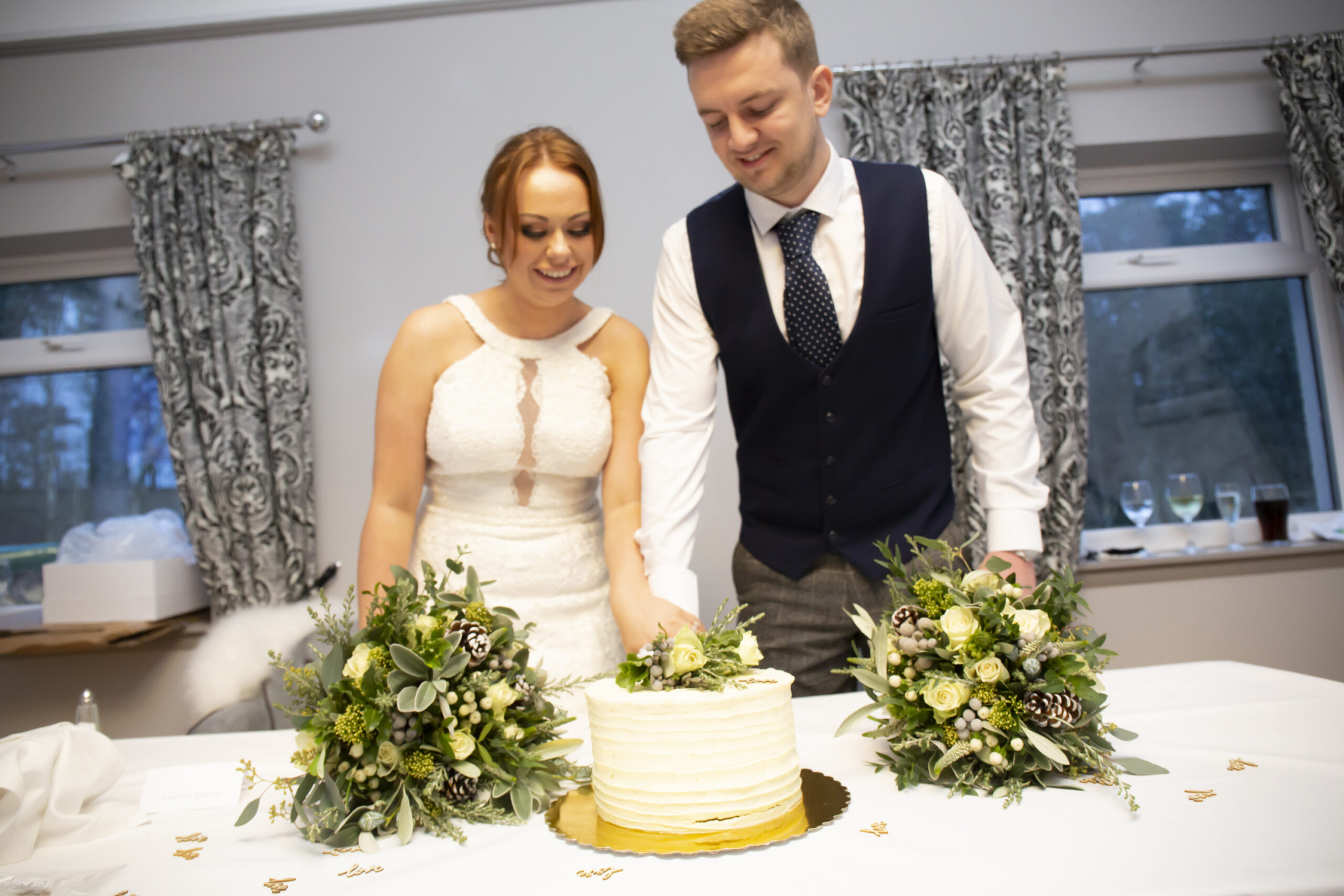bride and groom cut the wedding cake at gretna green hotel