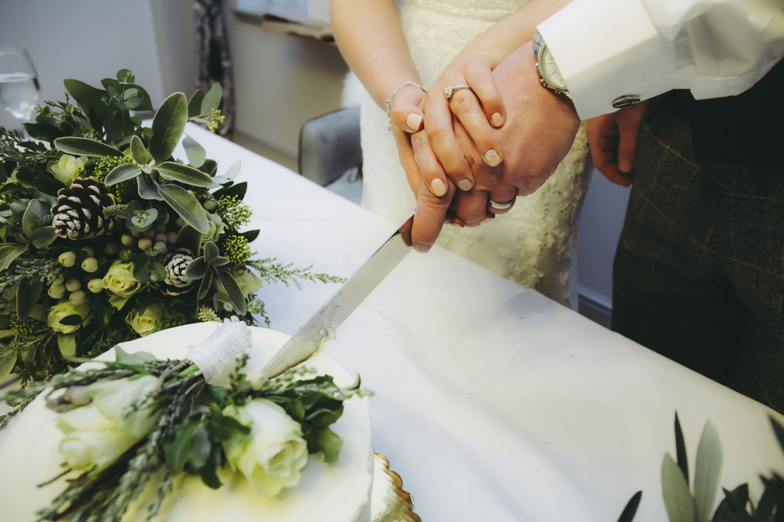 close up hands shot of the bride and groom cutting the wedding cake at gretna green hotel