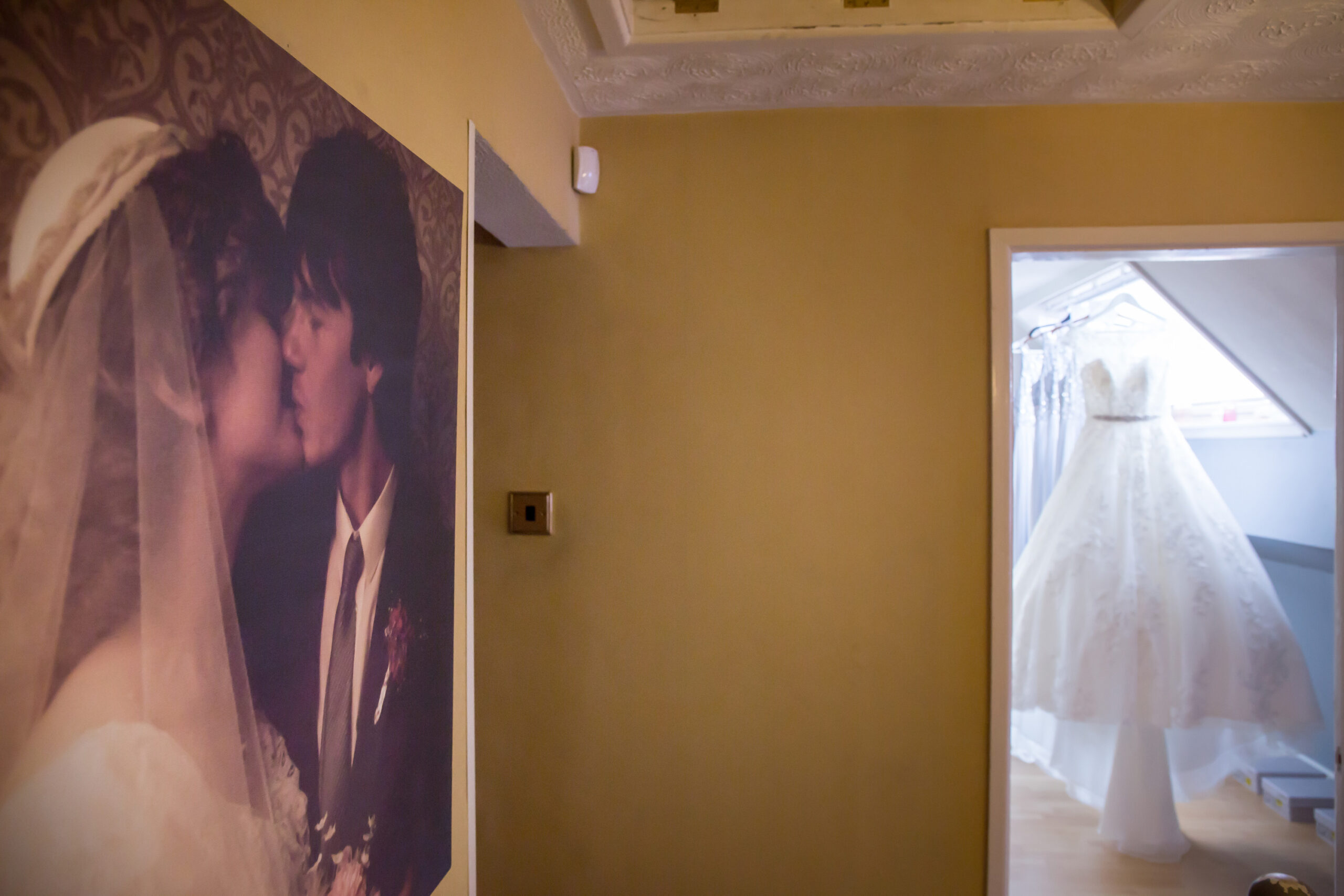 wedding dress hangs in a room with a photo of the mother and father of the bride's wedding day in the hallway