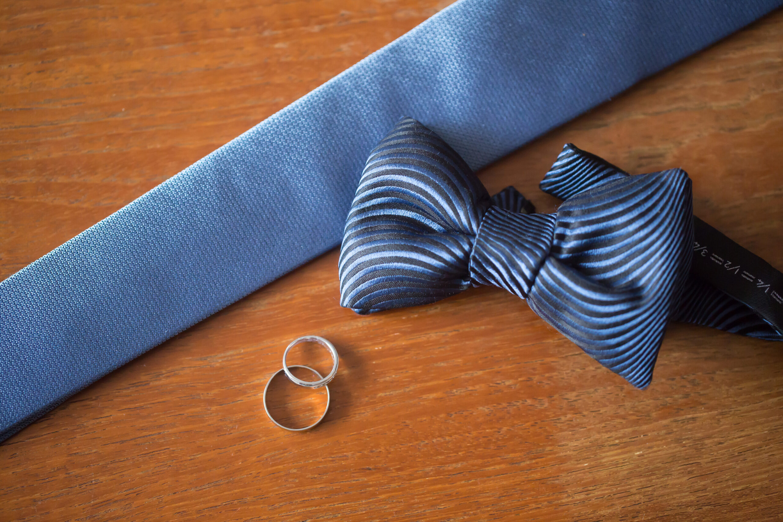 shot of the tie, bow tie and the wedding rings