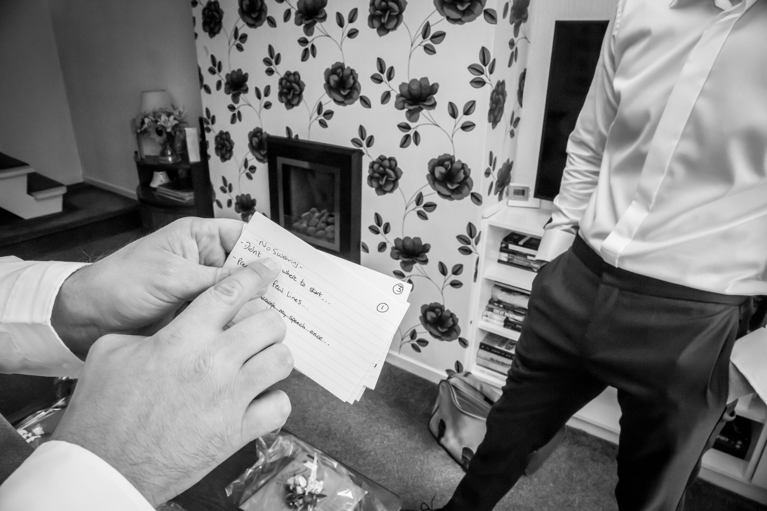 the best man points to the speech cards in front of the groom