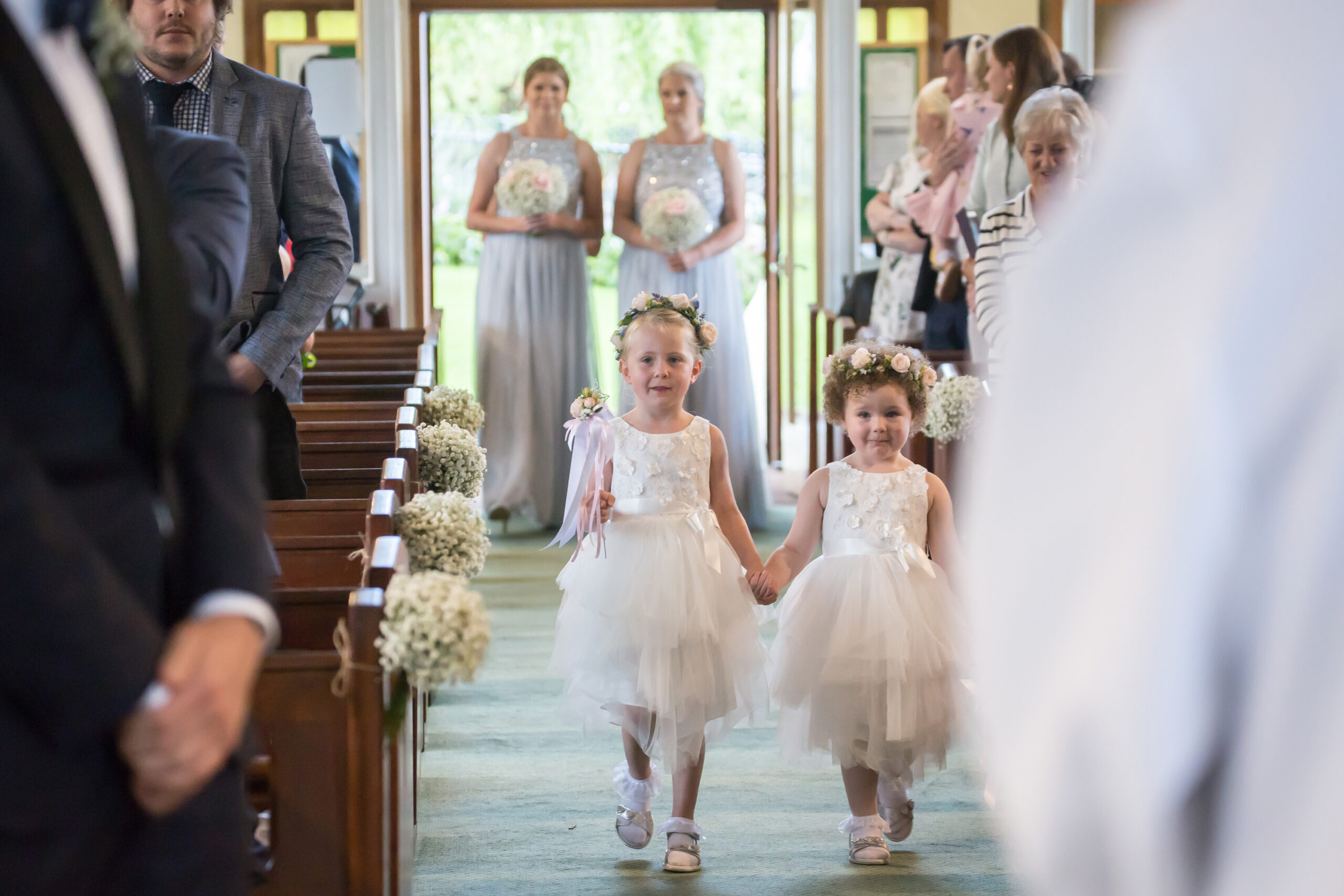 flower girls walk down the aisle at st hilda's in tottingham