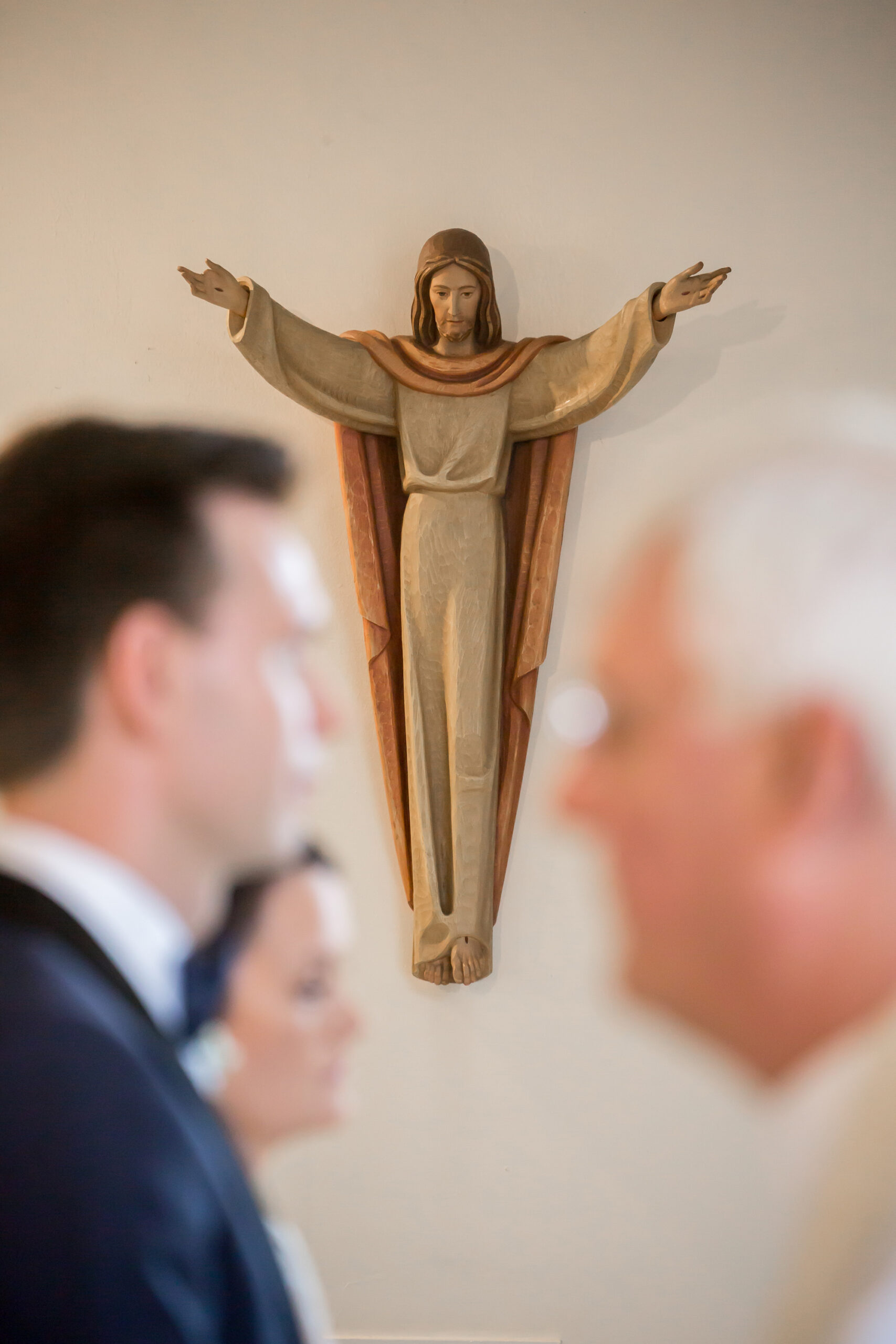 shot of a statue of christ during the wedding ceremony with bride and groom and priest out of focus in the foreground