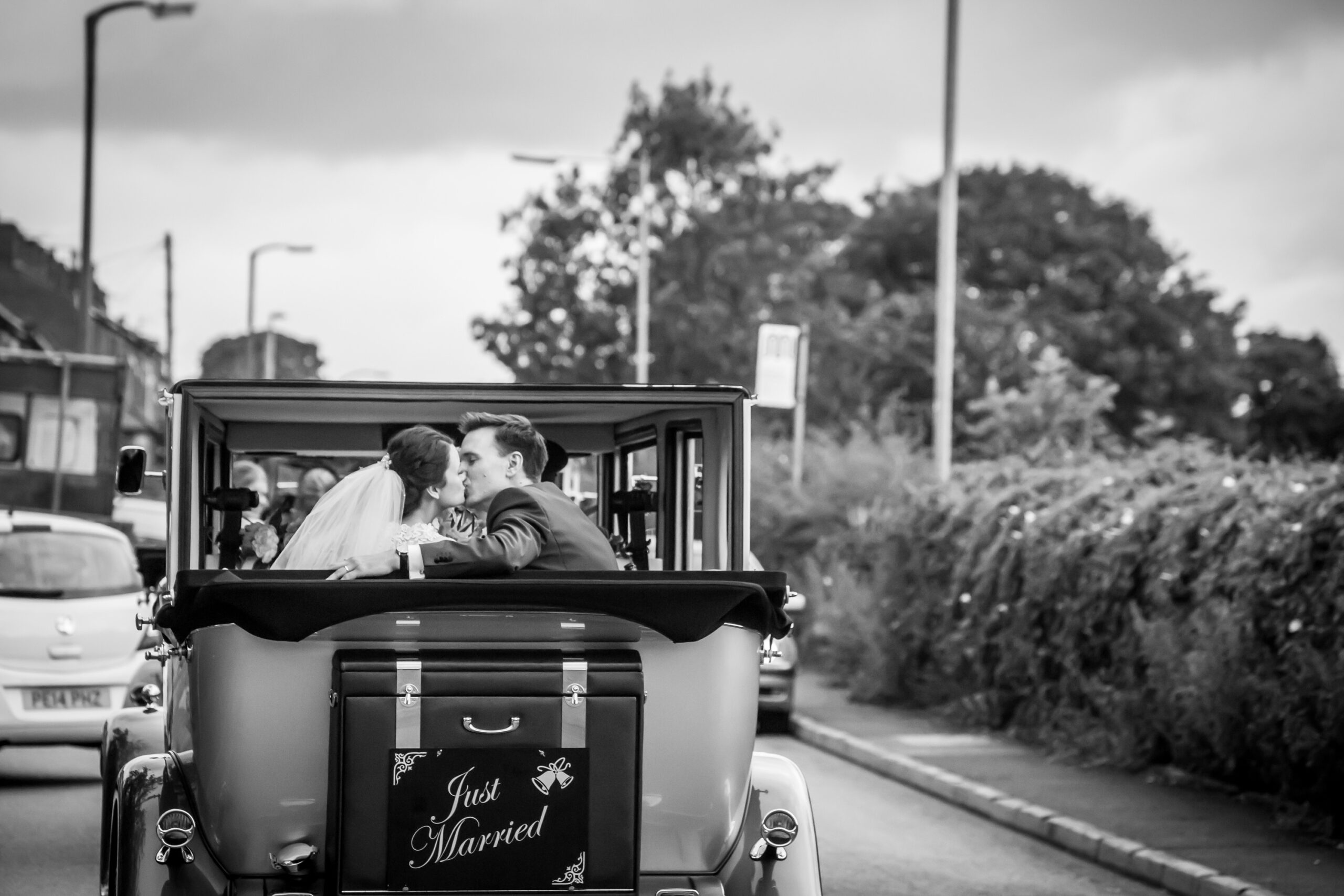 a view from the back of the bride and groom kissing in the back of a classic wedding car