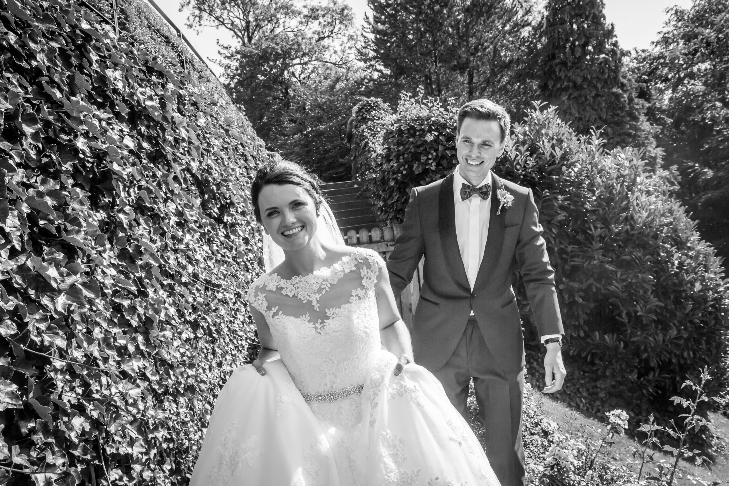bride and groom walk down the steps in the gardens of Mitton Hall, Whalley