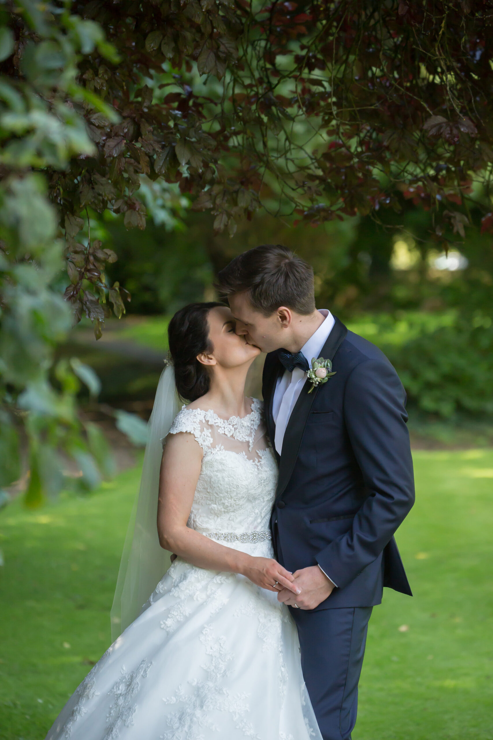 bride and groom kiss in the gardens of Mitton Hall