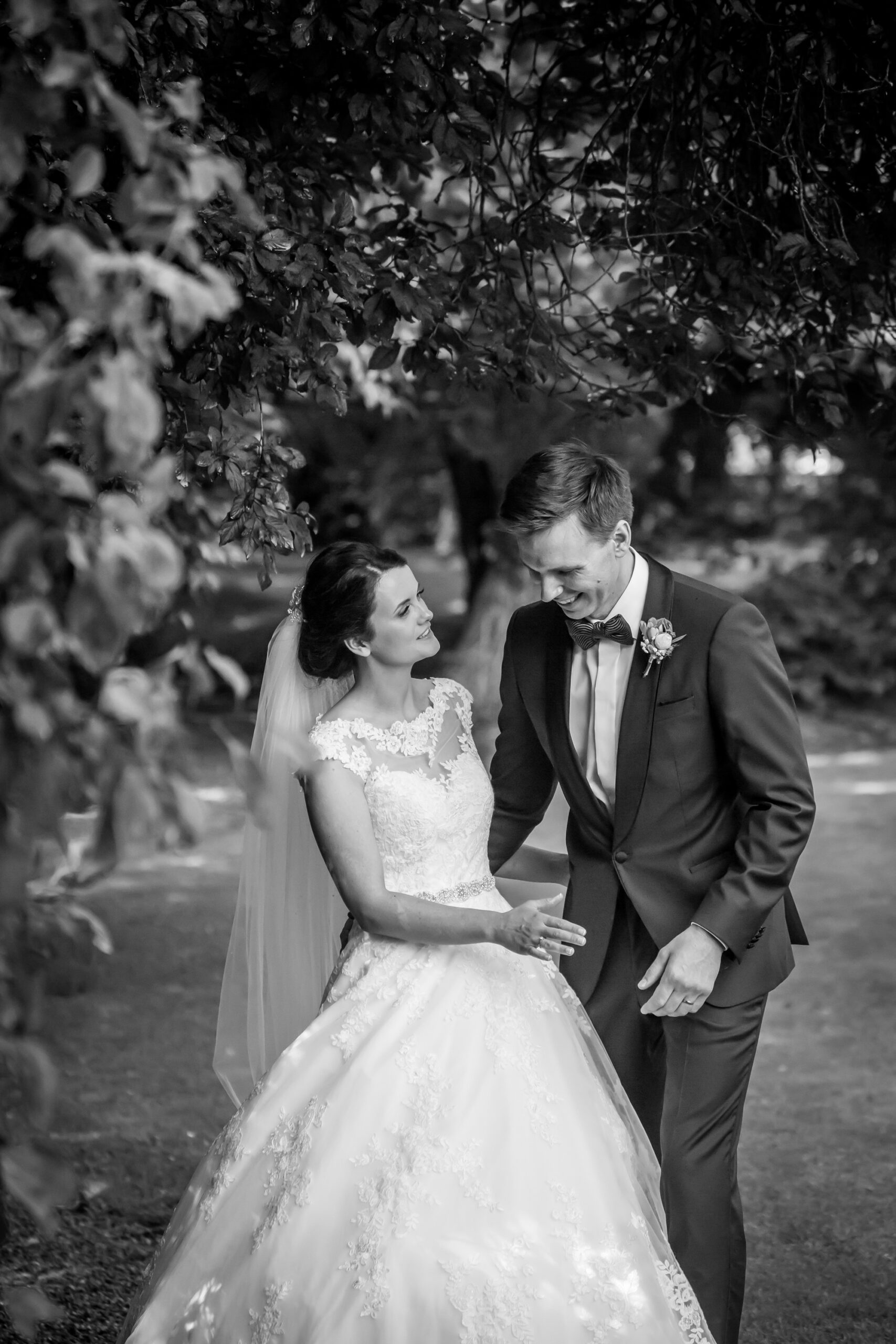 bride and groom take romantic walk in the gardens of Mitton Hall