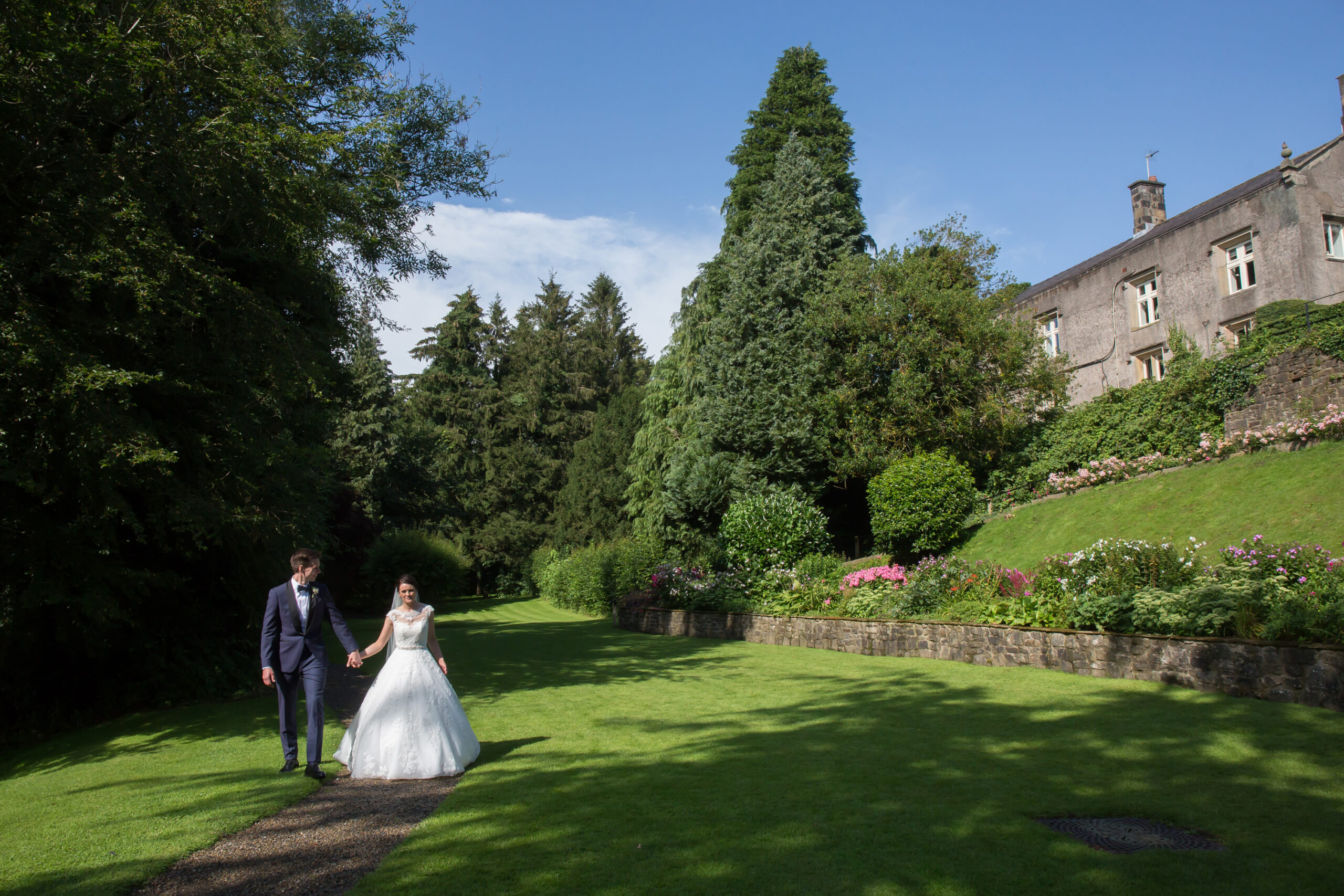 the happy couple go for a walk in the gardens of Mitton Hall
