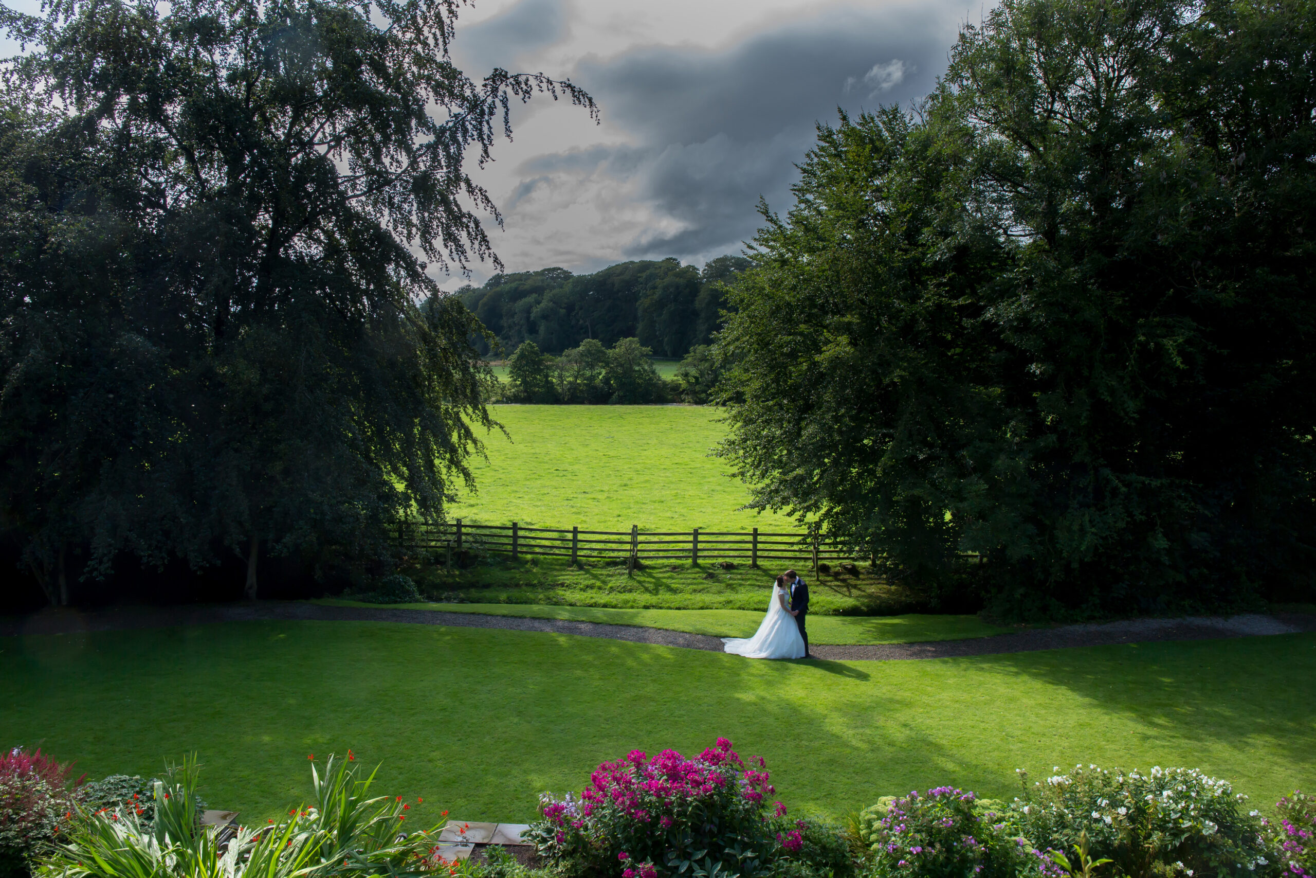 the bride and groom embrace in a wide landscape photo in the gardens of mitton hall