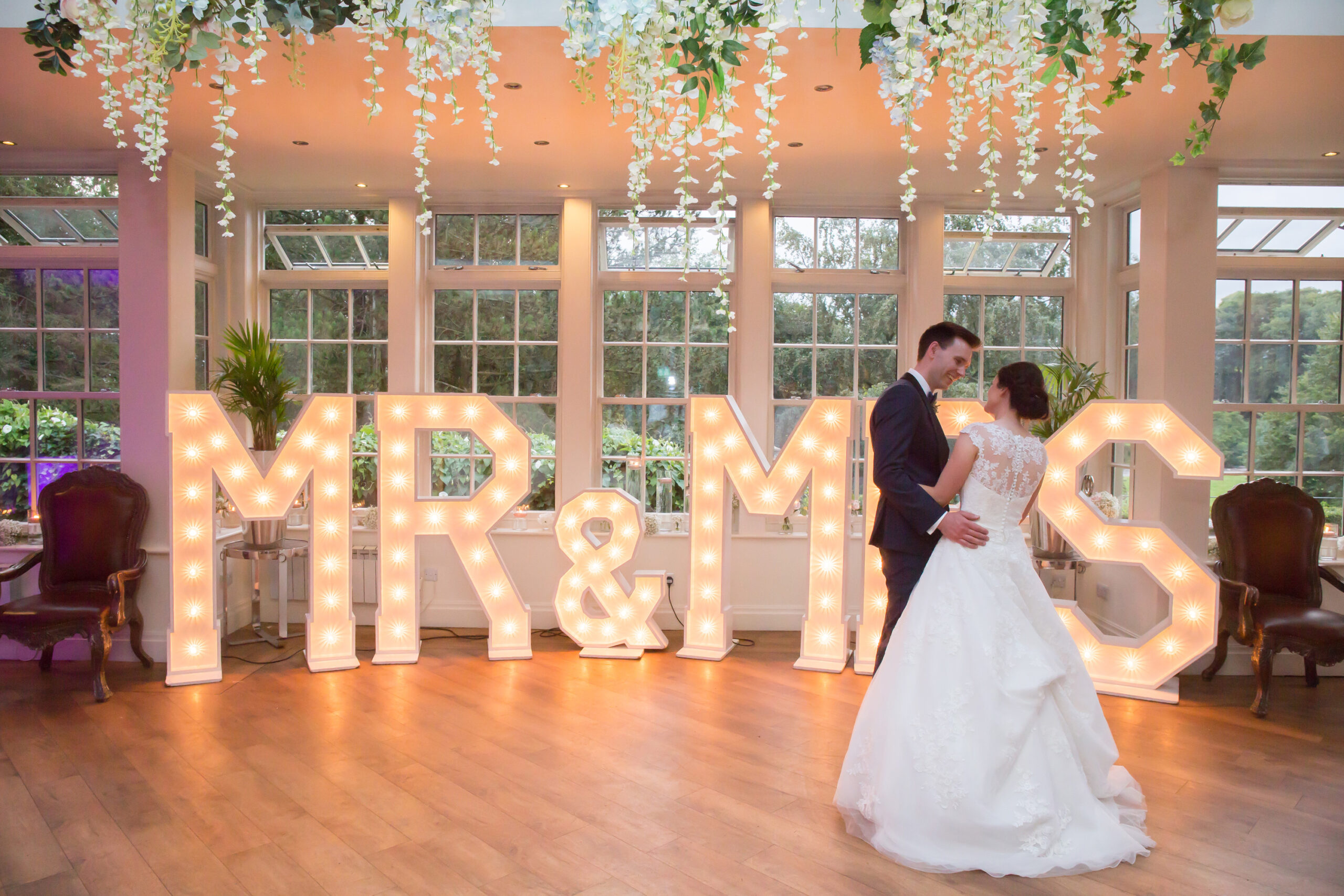 bride and groom have their first dance in front of mr & mrs sign