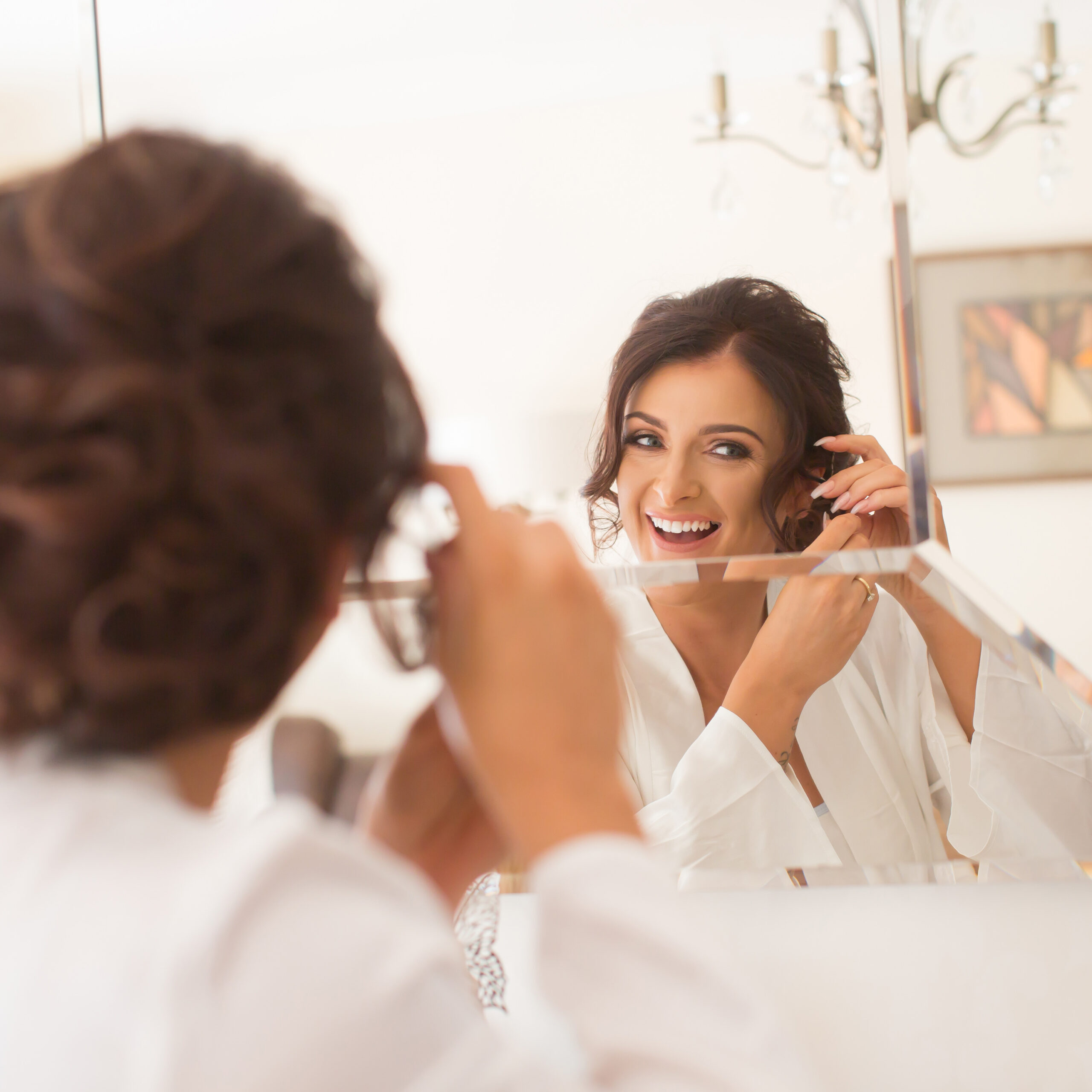 the groom adjusts his bow tie in the mirror