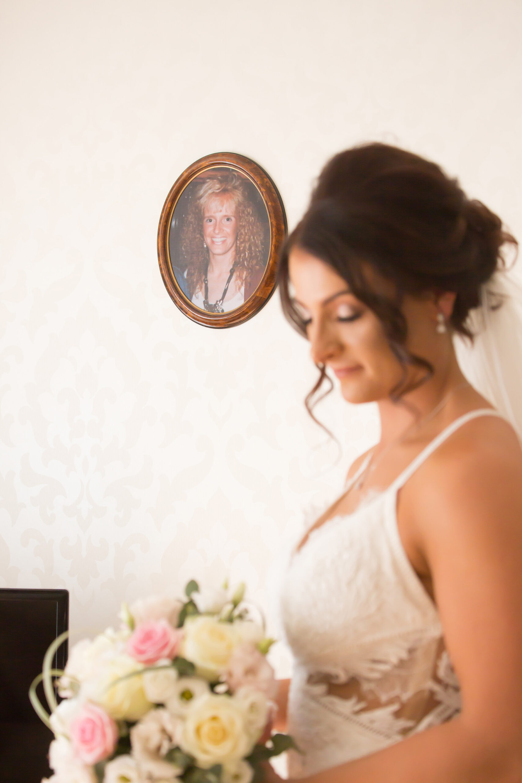 bride looks down with a photo of her mum in the background
