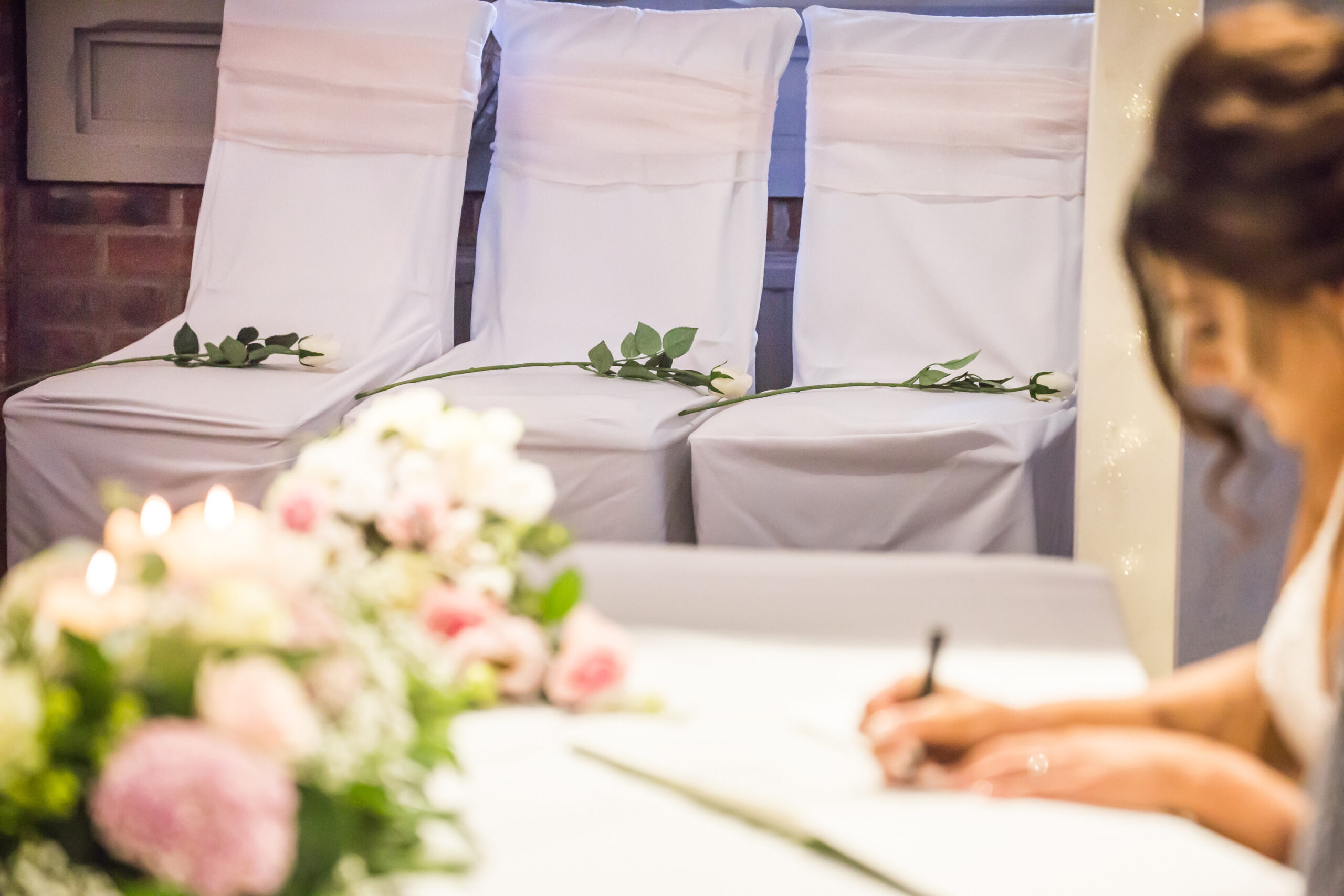 Three roses on chairs remembering loved ones as the bride signs the marriage register